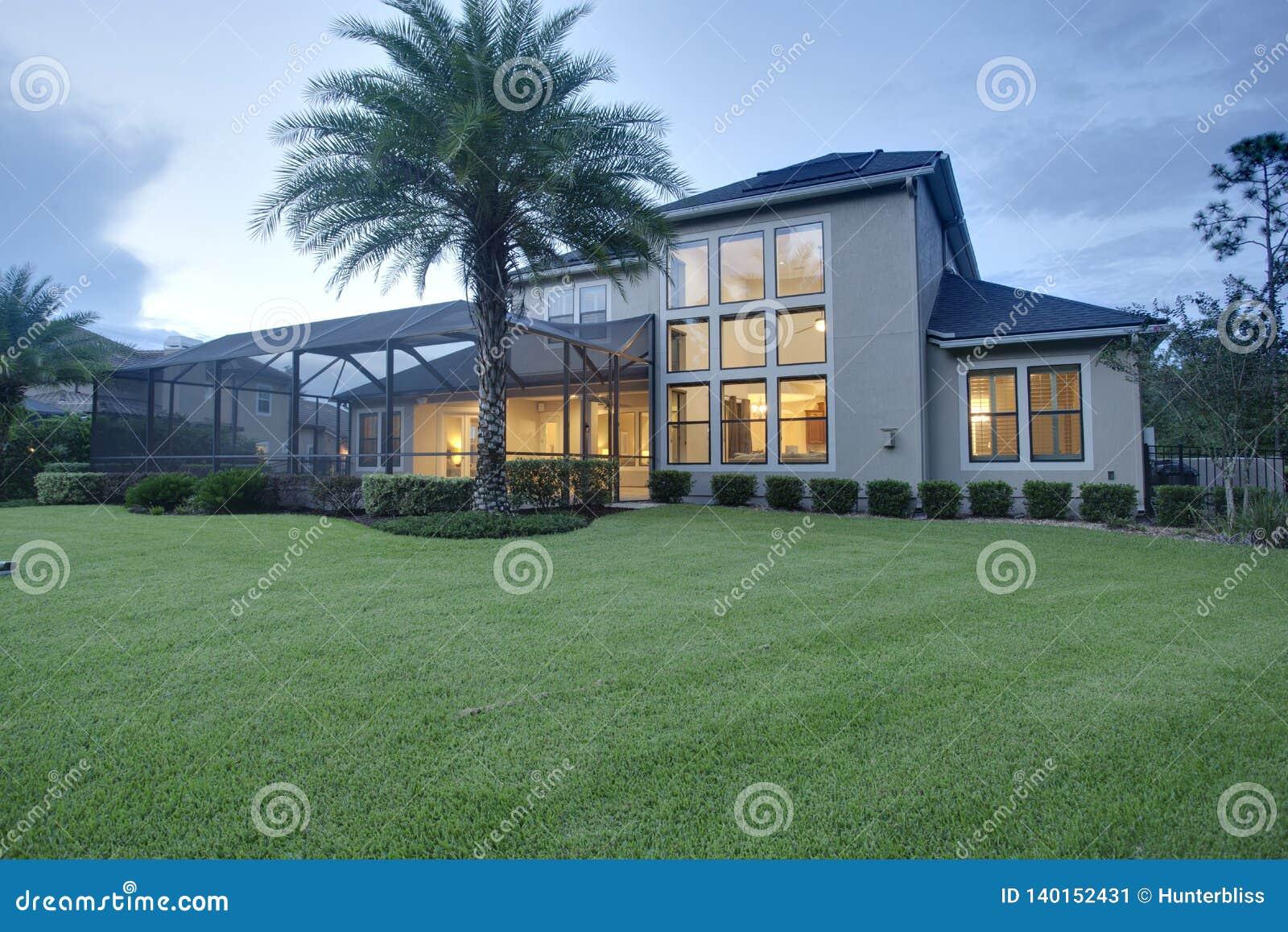豪华家庭外部建筑黄昏黎明夜草坪日落内部的光转动在水平的取向风景