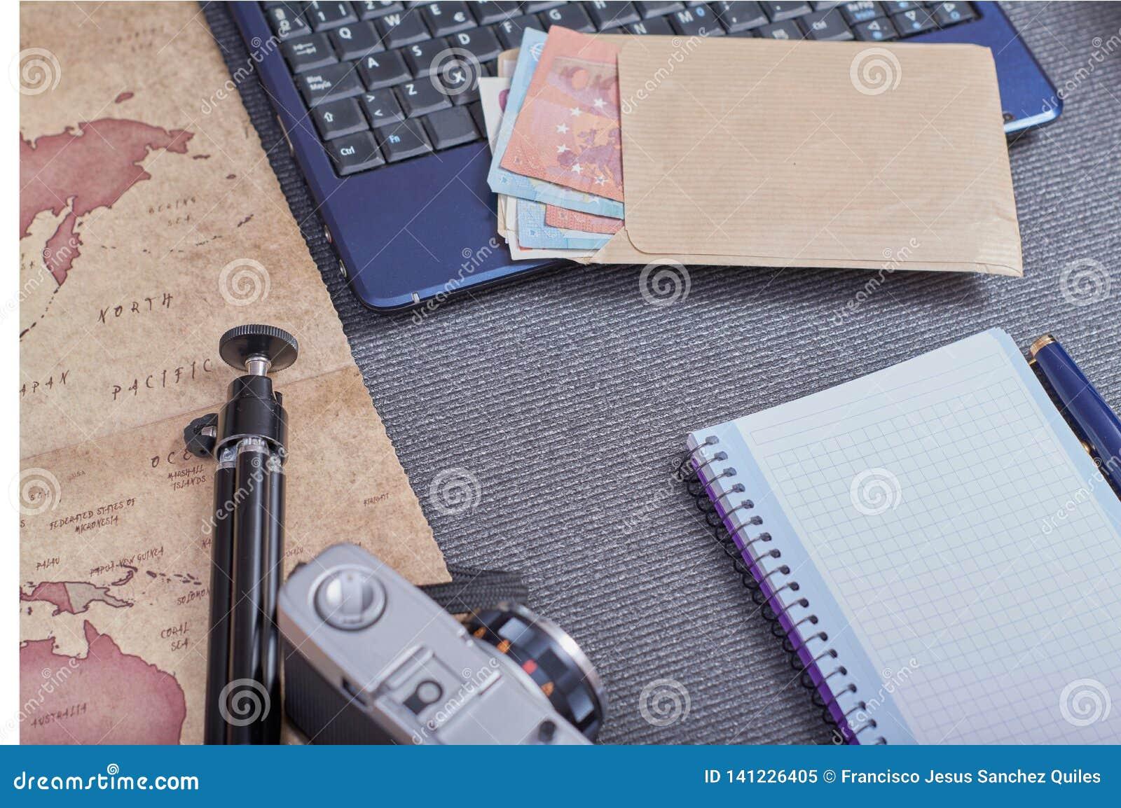 葡萄酒在膝上型计算机旁边的照片照相机和与金钱的一个信封在欧元