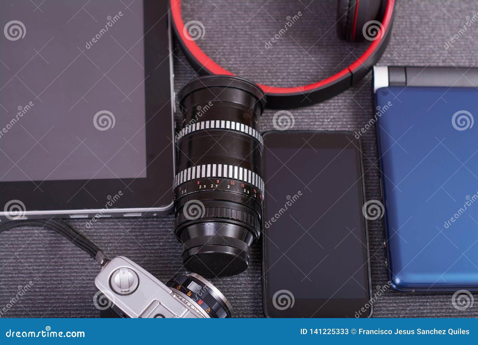 葡萄酒在膝上型计算机旁边的照片照相机片剂和智能手机