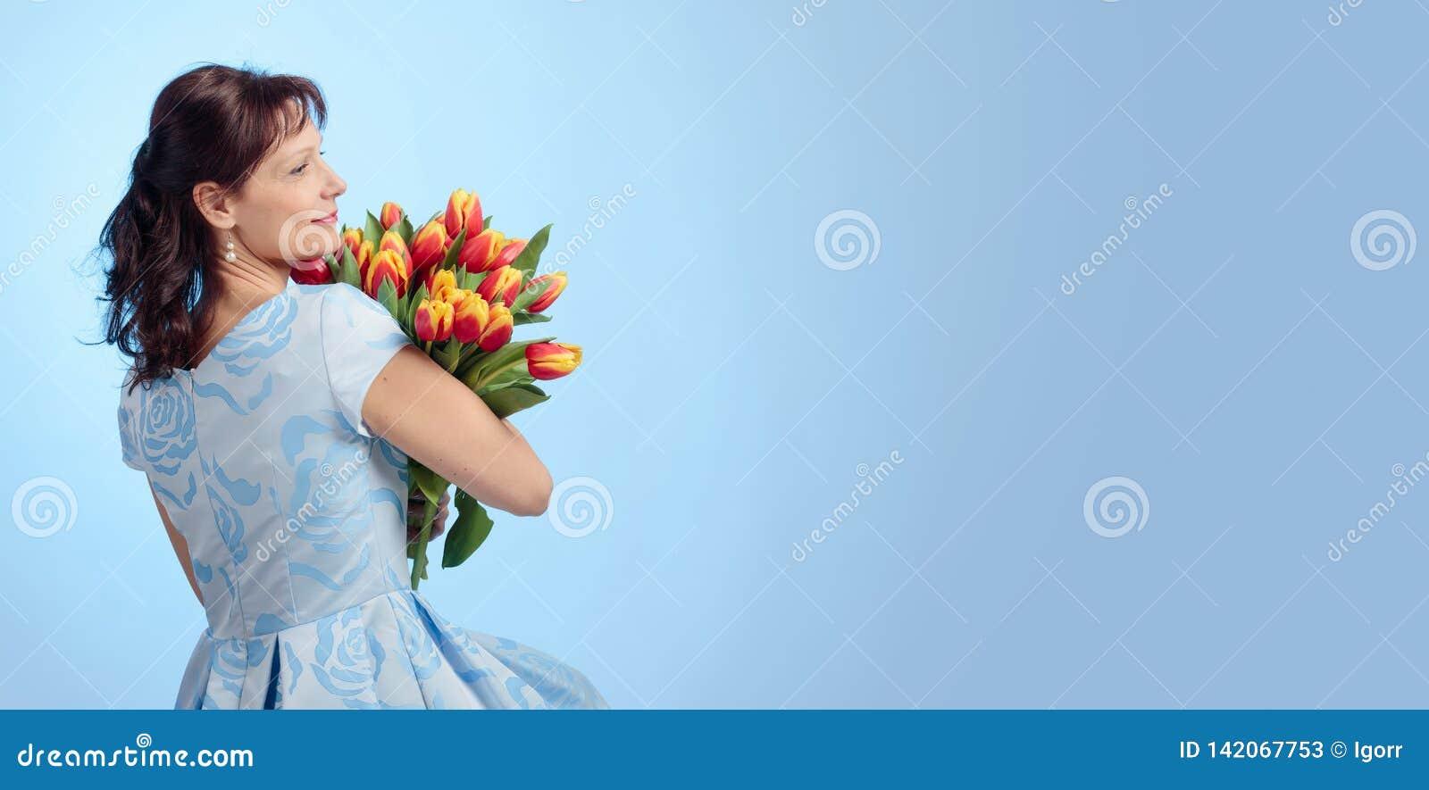 蓝色礼服的可爱的妇女有红色和黄色郁金香花束的