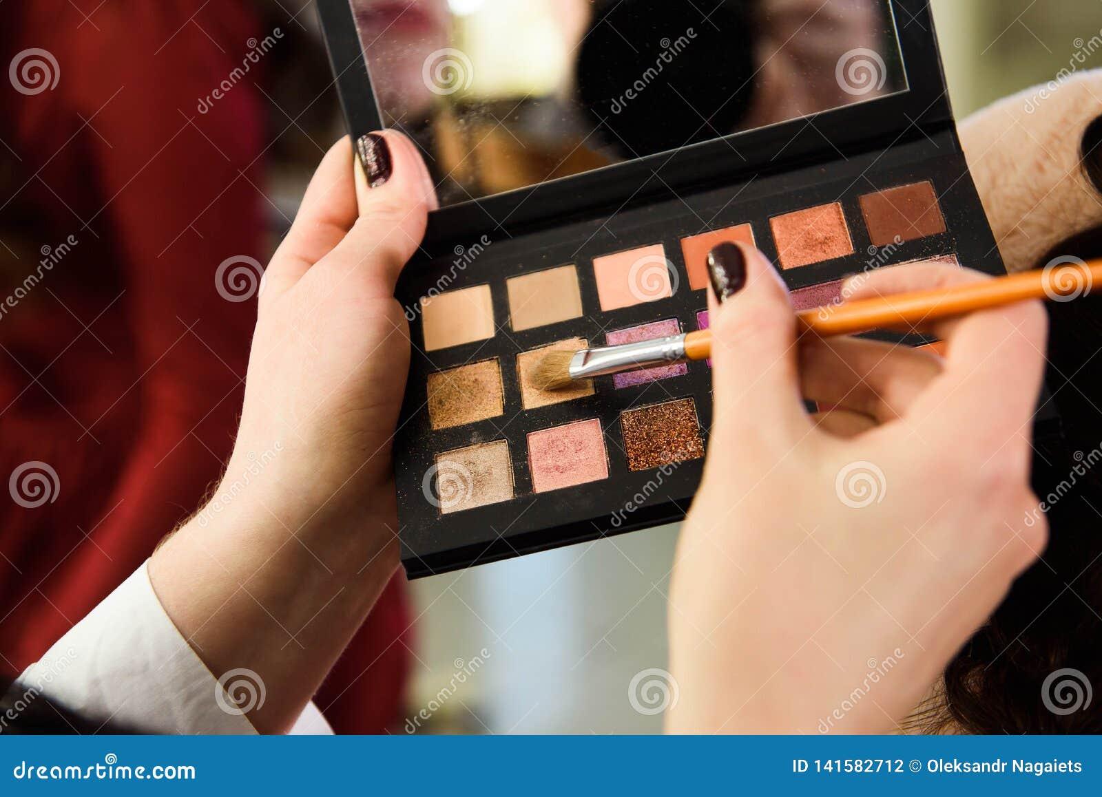 脸概念 妇女得到的关闭在眼皮组成 应用与刷子的眼影膏由专业艺术家