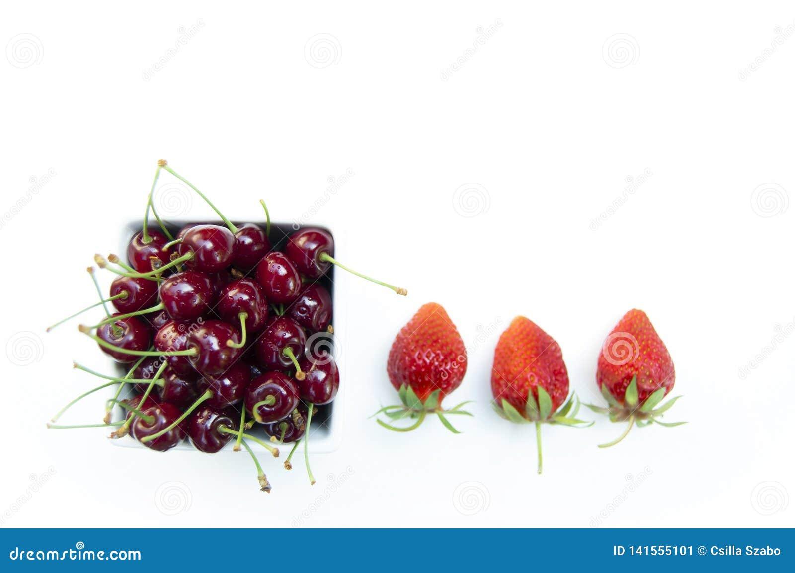 顶面射击,关闭与水下落的新鲜的甜樱桃在白色在白色背景隔绝的碗和草莓,有选择性