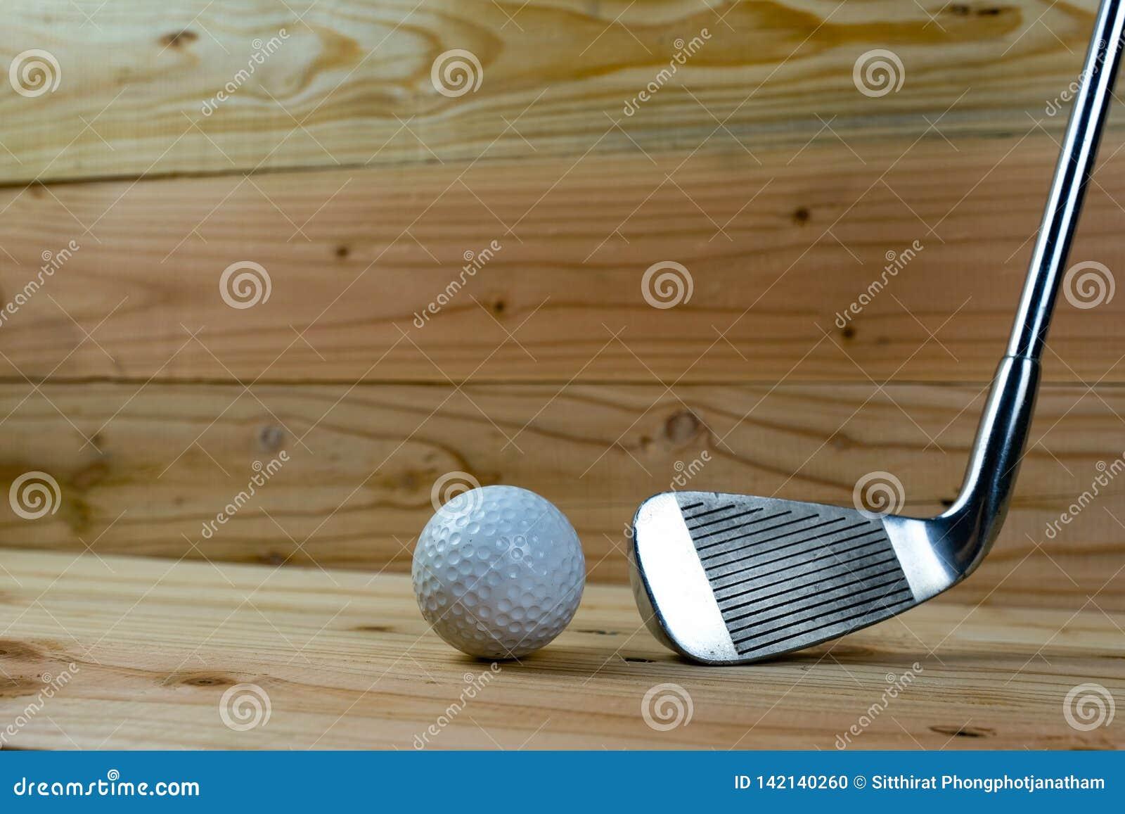 高尔夫球和高尔夫俱乐部在木地板上