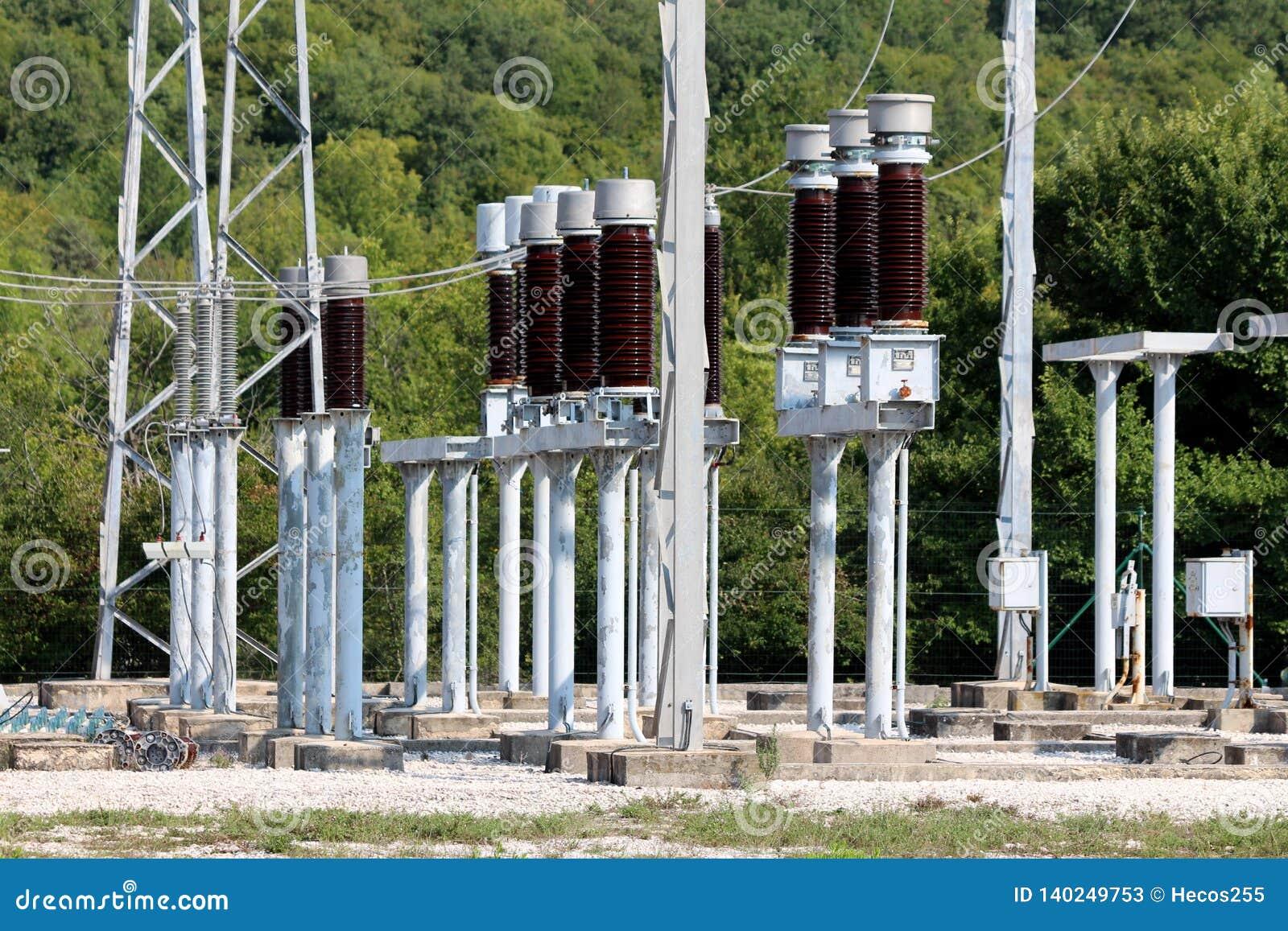 高黑褐色陶瓷绝缘体登上在金属管子和和在地方能源厂里面的电线有关围拢了