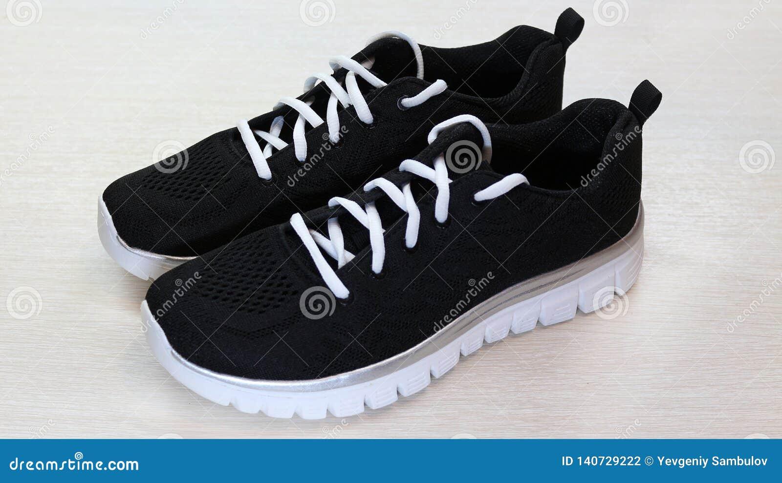 黑有白色单一和白色鞋带的体育男女皆宜的运动鞋在白色背景