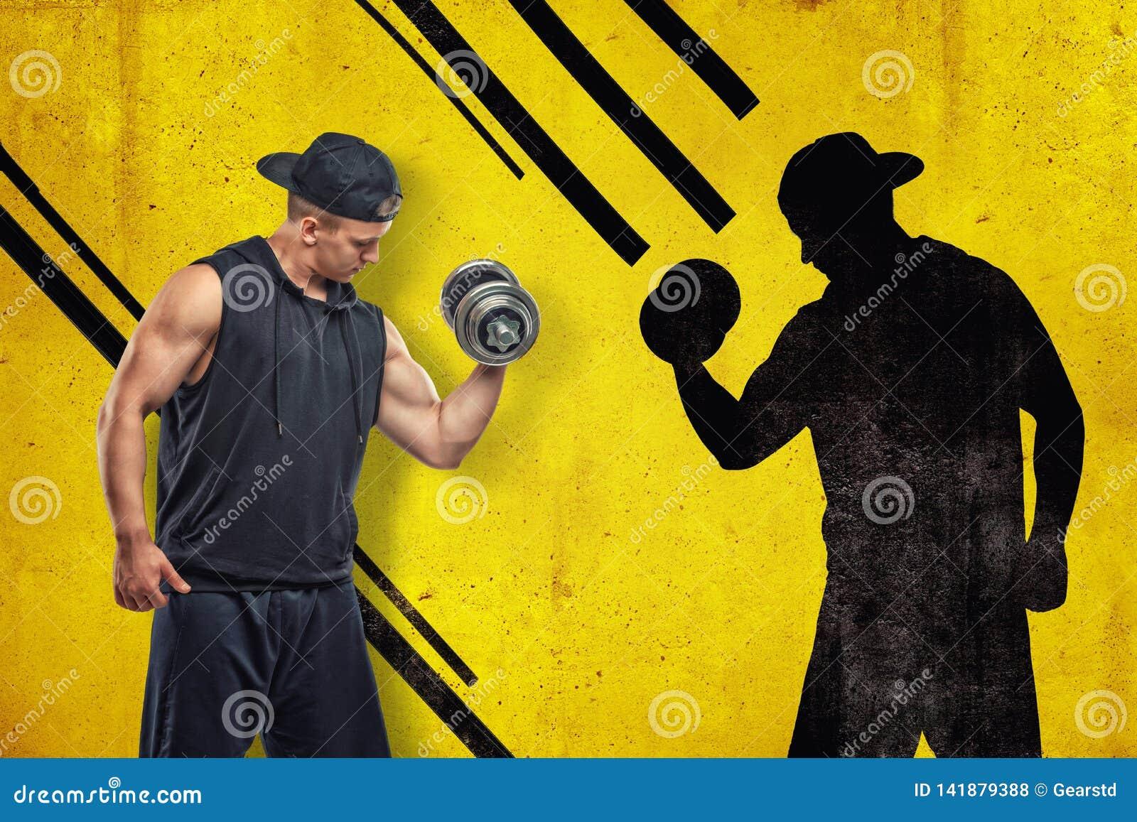 黑运动服的坚强的肌肉年轻人有与黑阴影的一个哑铃的在黄色背景