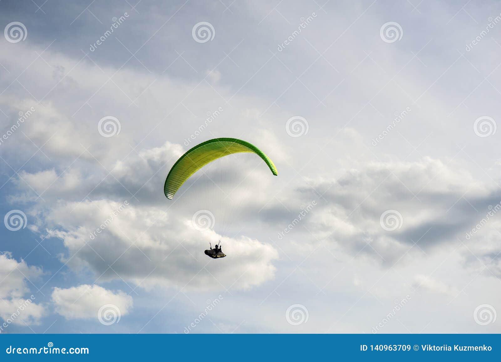黄色和绿色滑翔伞是在天空蔚蓝的飞行以云彩为背景