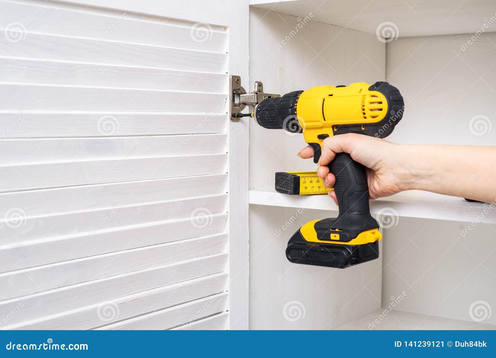 黄色螺丝刀在一只女性手上 家具铰链的设施在橱门的