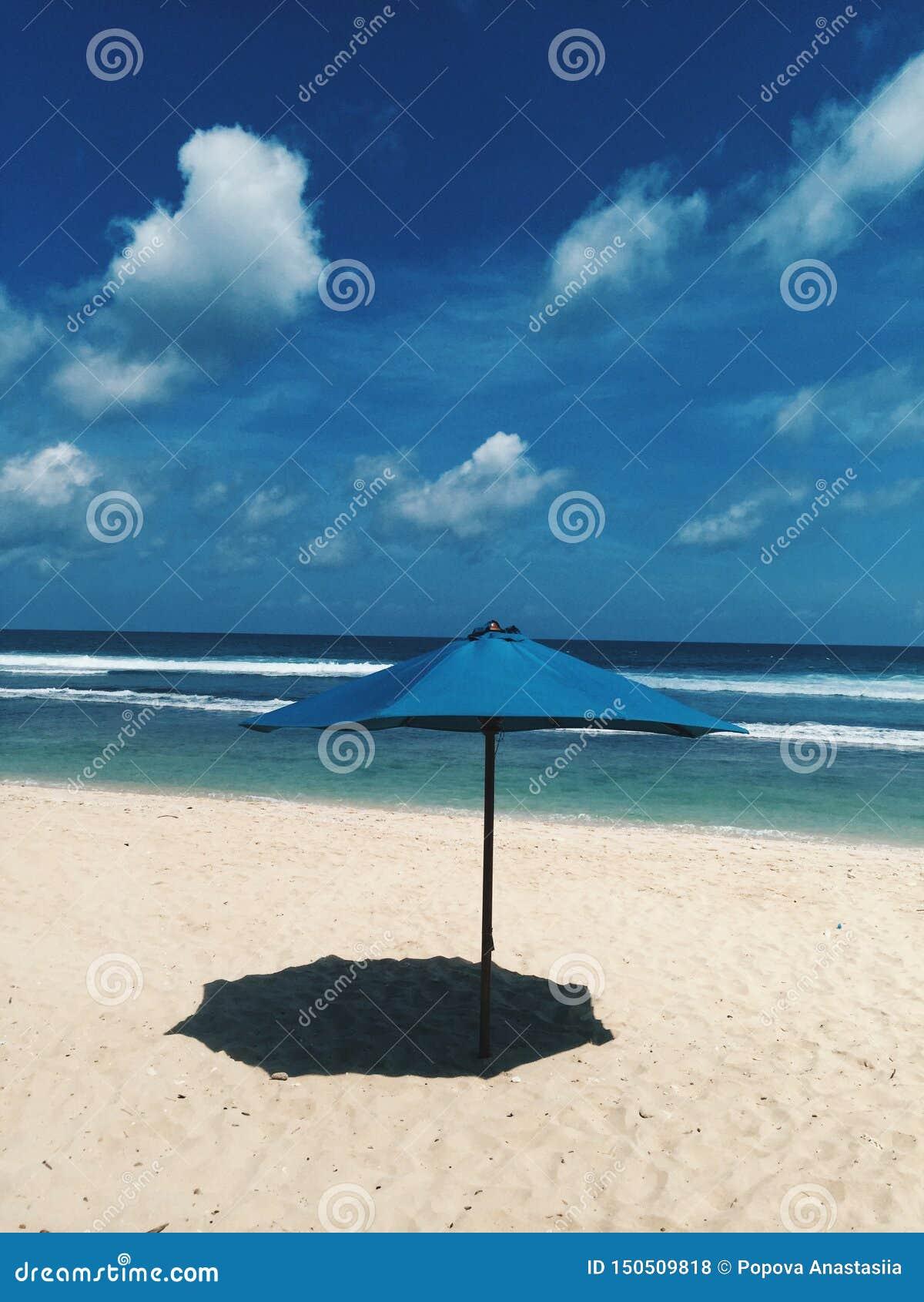Één blauwe paraplu van de strandzon maakt schaduw op het zand