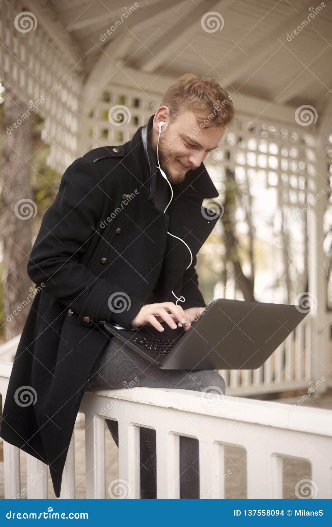 ??n gelukkige jonge mens, 20-29 jaar die oud, op omheining in openlucht in park zitten, terwijl het gebruiken van zijn laptop