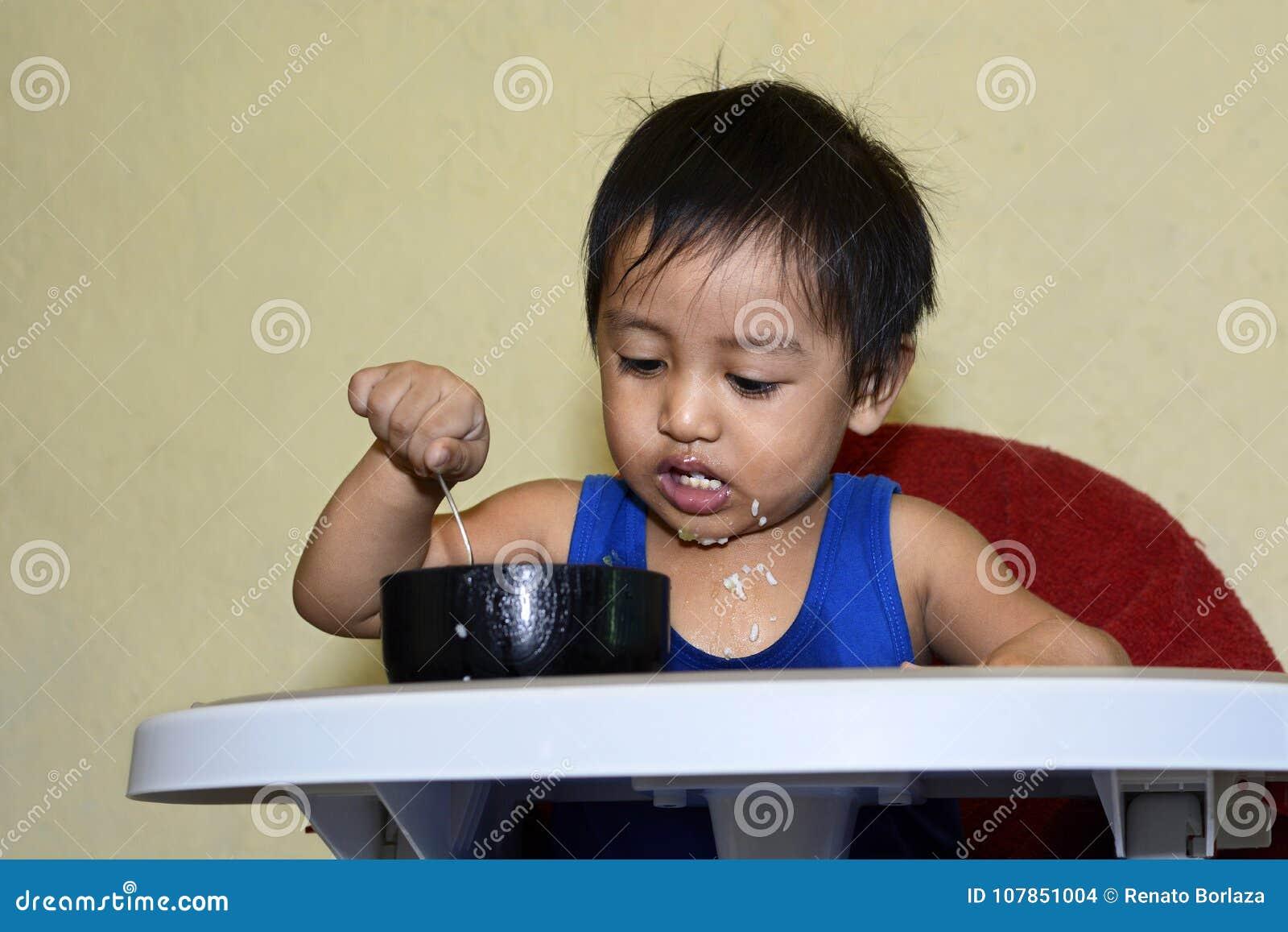 Één jongen die van de 1 éénjarige Aziatische baby leren thuis zelf te eten, slordig op baby het dineren stoel