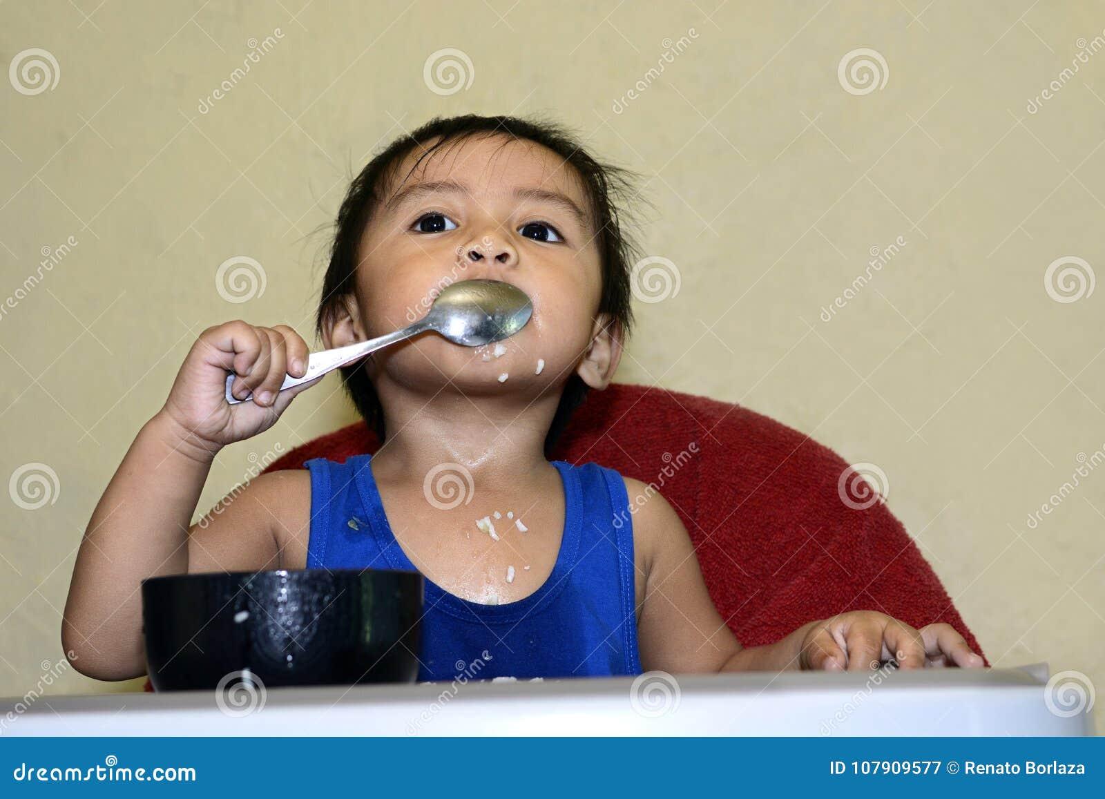 Één jongen die van de 1 éénjarige Aziatische baby zelf door lepel leren thuis te eten, slordig op baby het dineren stoel