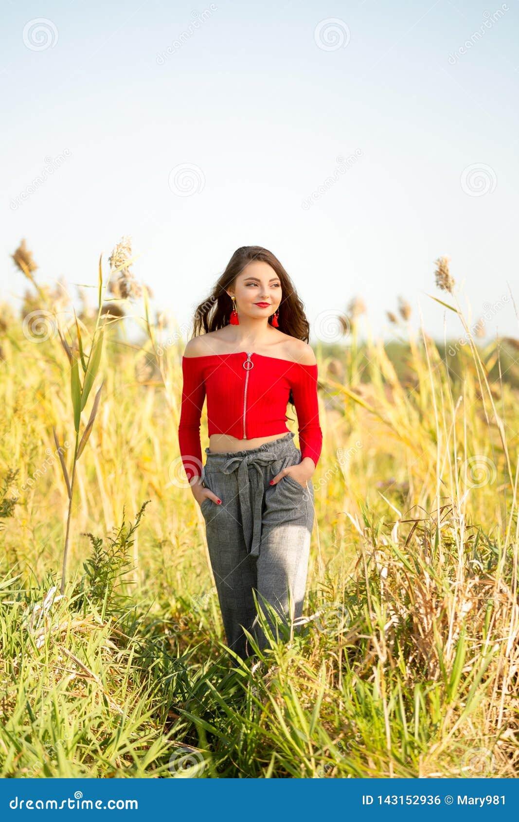 Één mooi vrouwelijk Kaukasisch middelbare school hoger meisje in rode gewassen hoogste sweater