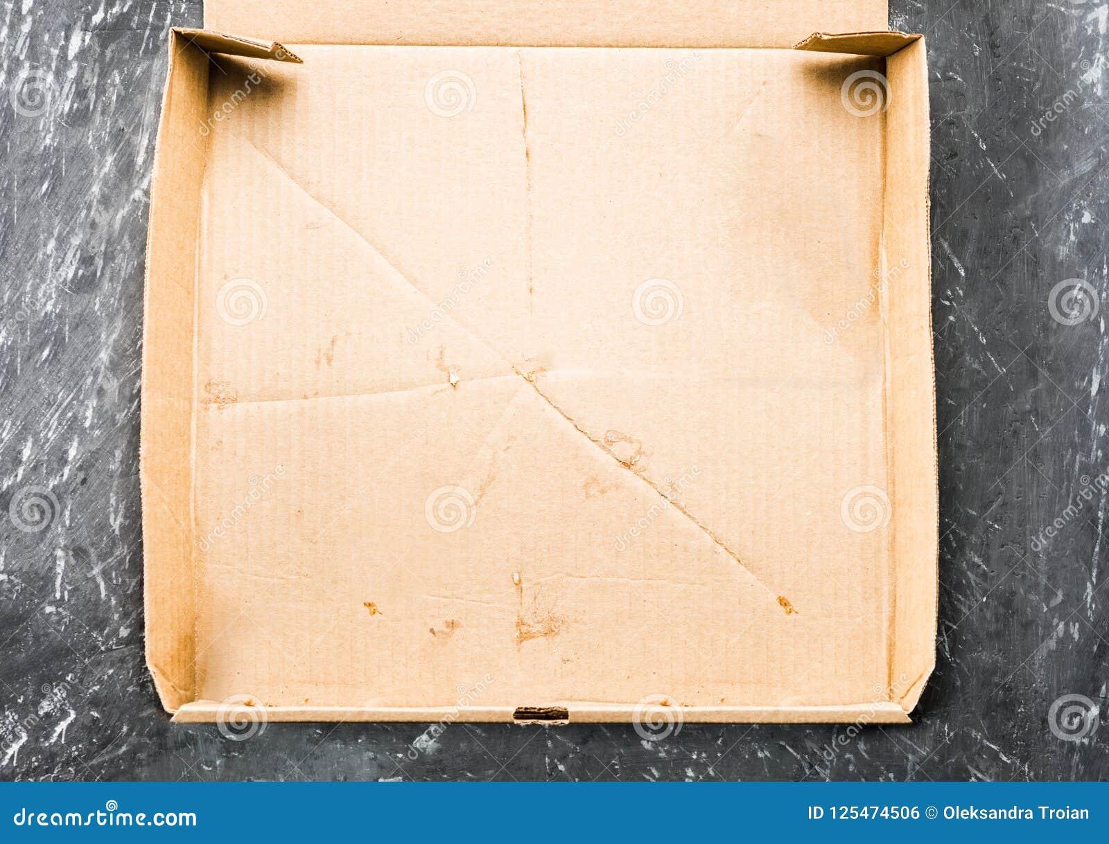 Één stuk van pizza in het vakje van de kartonpizza Hoogste mening van leeg vakje met exemplaarruimte op donker beton