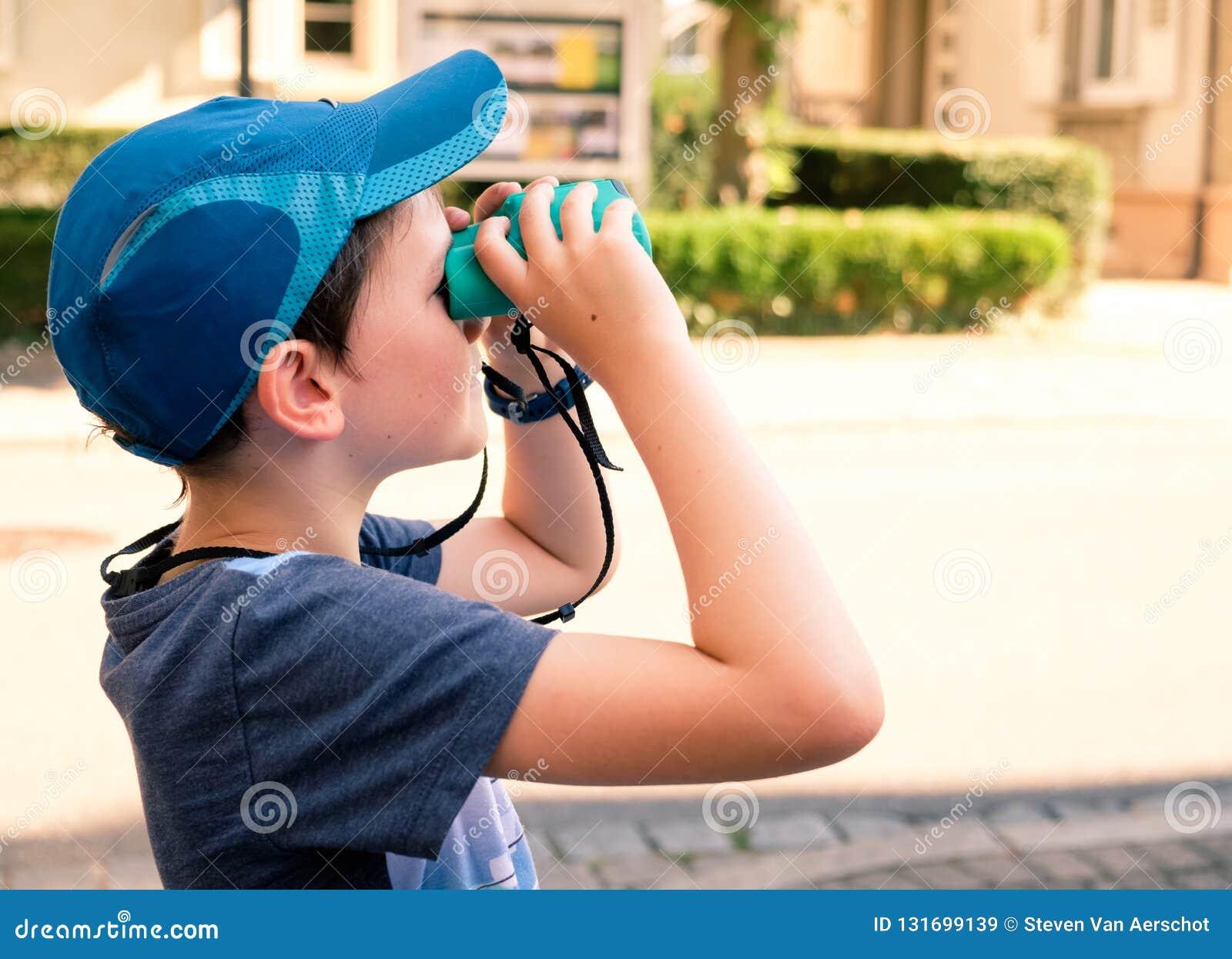 8 éénjarigenjongen die door verrekijkers kijken
