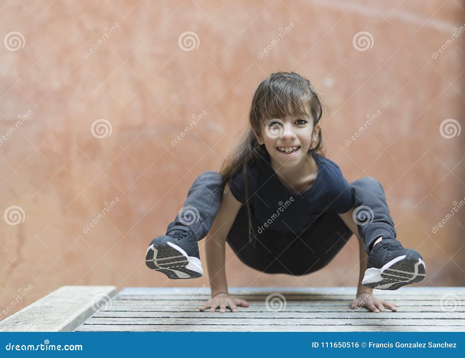 10 éénjarigenmeisje die een yogahouding doen