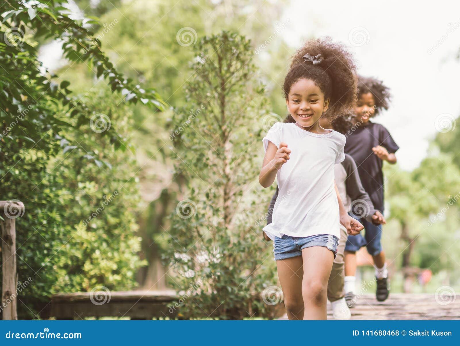 逗人喜爱小女孩使用室外 在公园的孩子和朋友愉快的戏剧