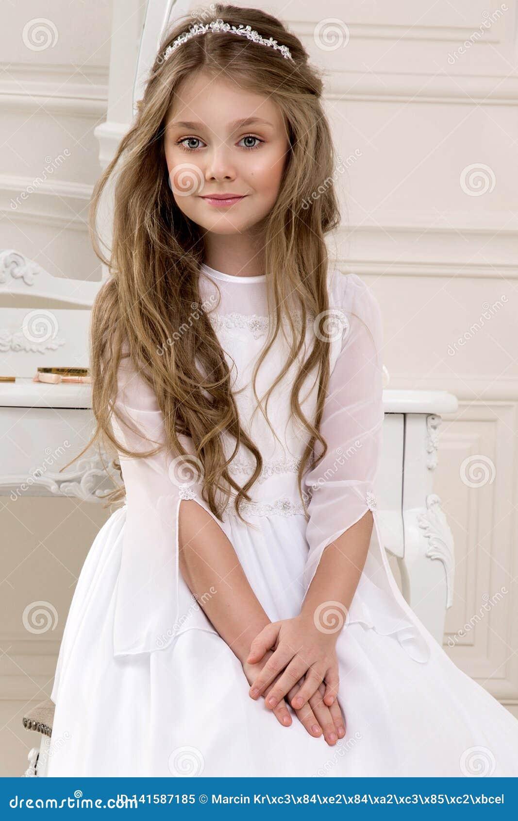 逗人喜爱的女孩画象白色礼服和花圈的在第一个圣餐背景教会门