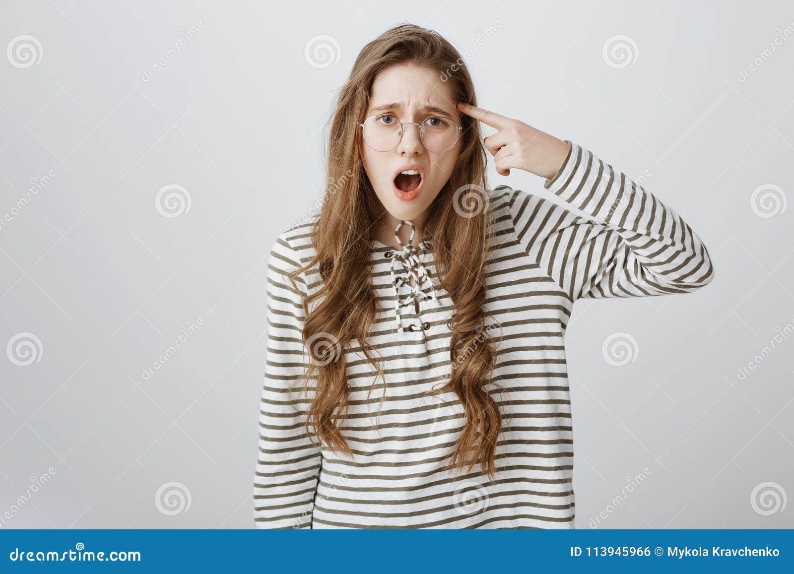 É você fora de sua mente Retrato do dedo caucasiano incomodado esperto do rolamento da menina sobre o templo, olhando de sobrance