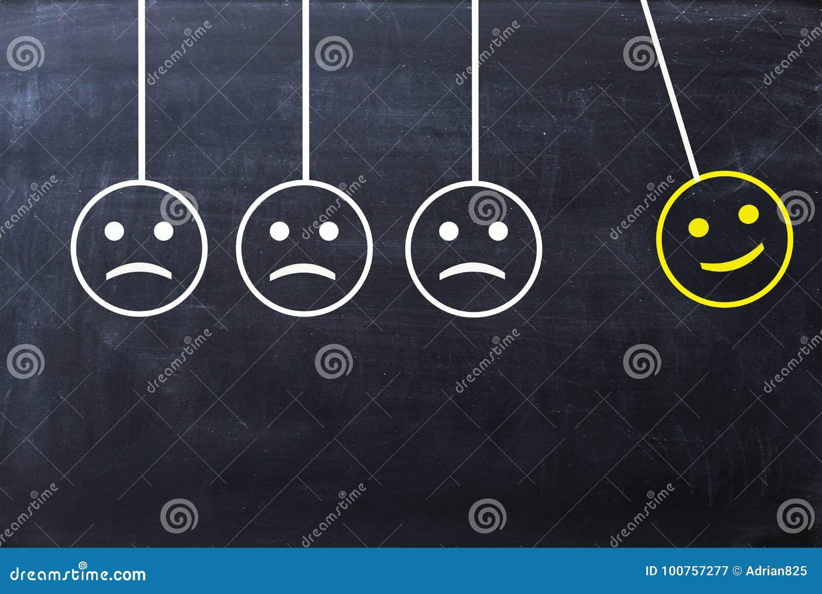 Écartez le concept de bonheur avec les visages heureux et tristes sur le berceau de newton's sur le tableau noir