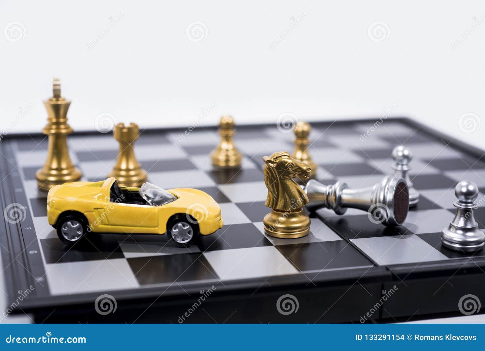 Échiquier d isolement sur le fond blanc Figures d or et argentées avec la petite voiture jaune