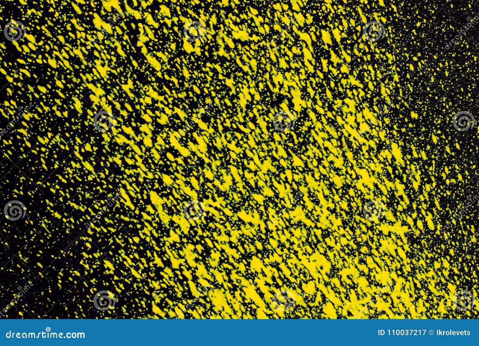 Éclabousse de la peinture jaune d aérosol sur une surface noire Fond,