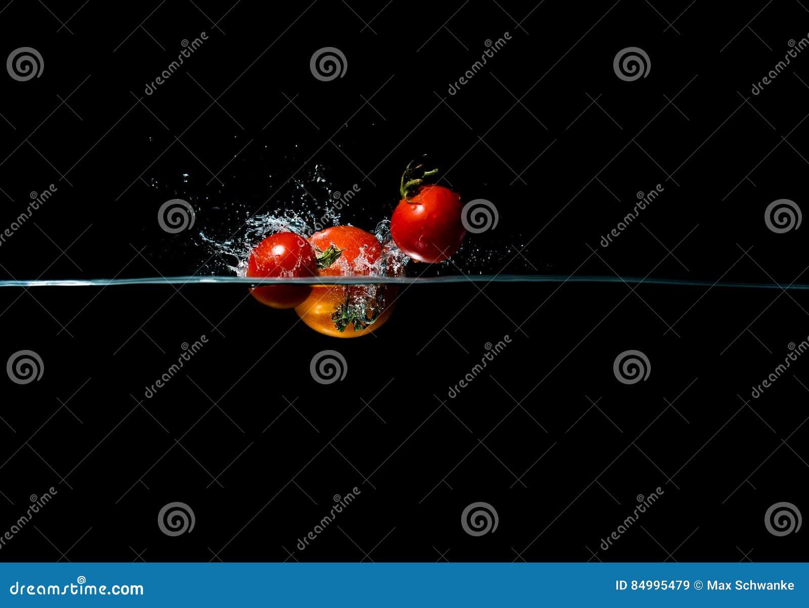 Éclaboussure de tomate de photographie à grande vitesse dans l eau