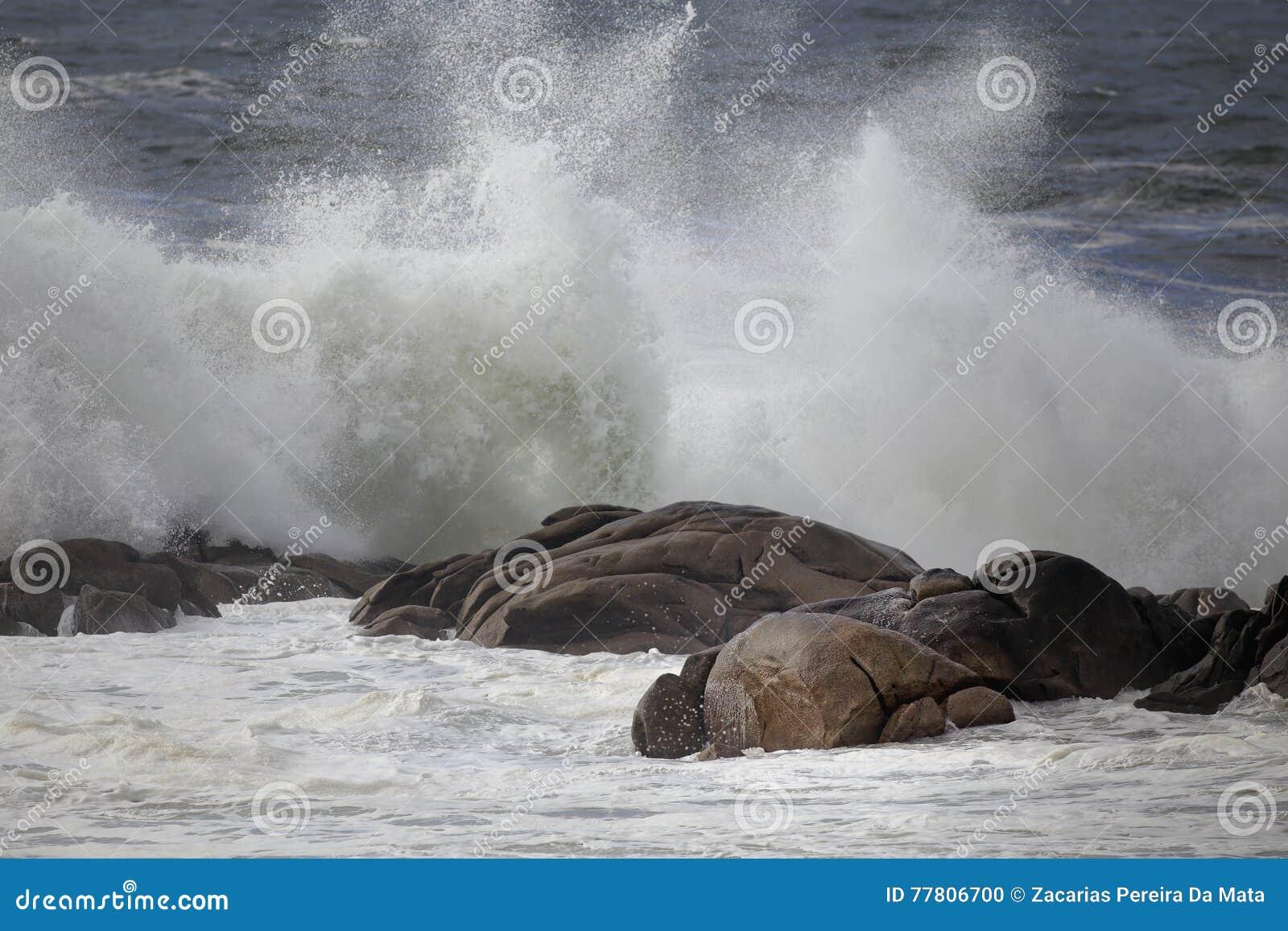 Éclaboussure de vague contre des roches