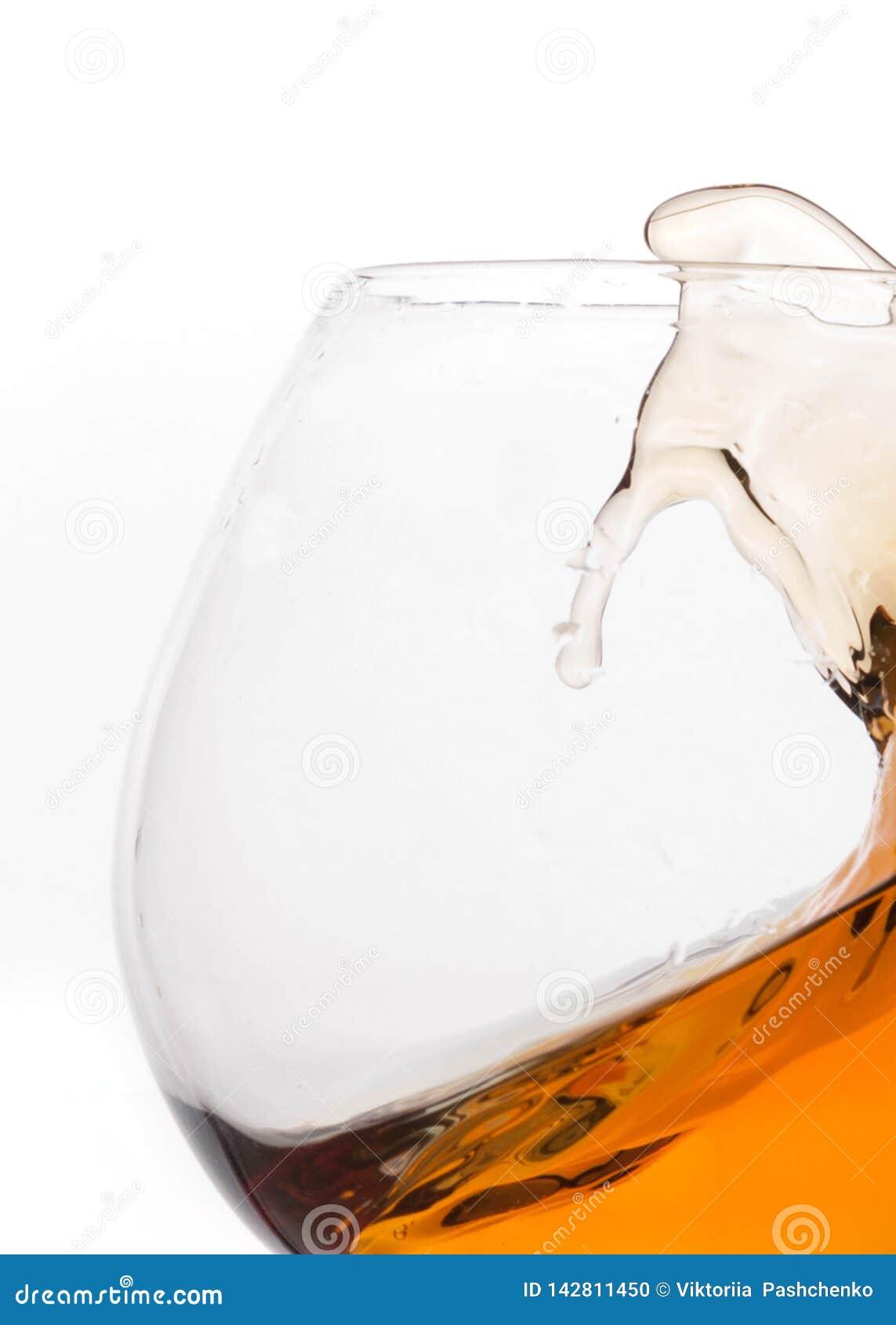 Éclaboussure de whiskey brun en verre transparent avec la réflexion