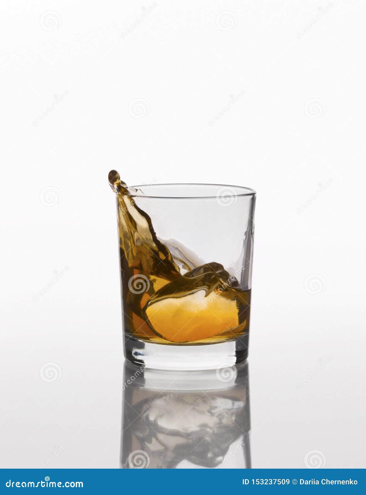 Éclaboussure de whiskey sur le verre élégant d isolement sur le fond blanc
