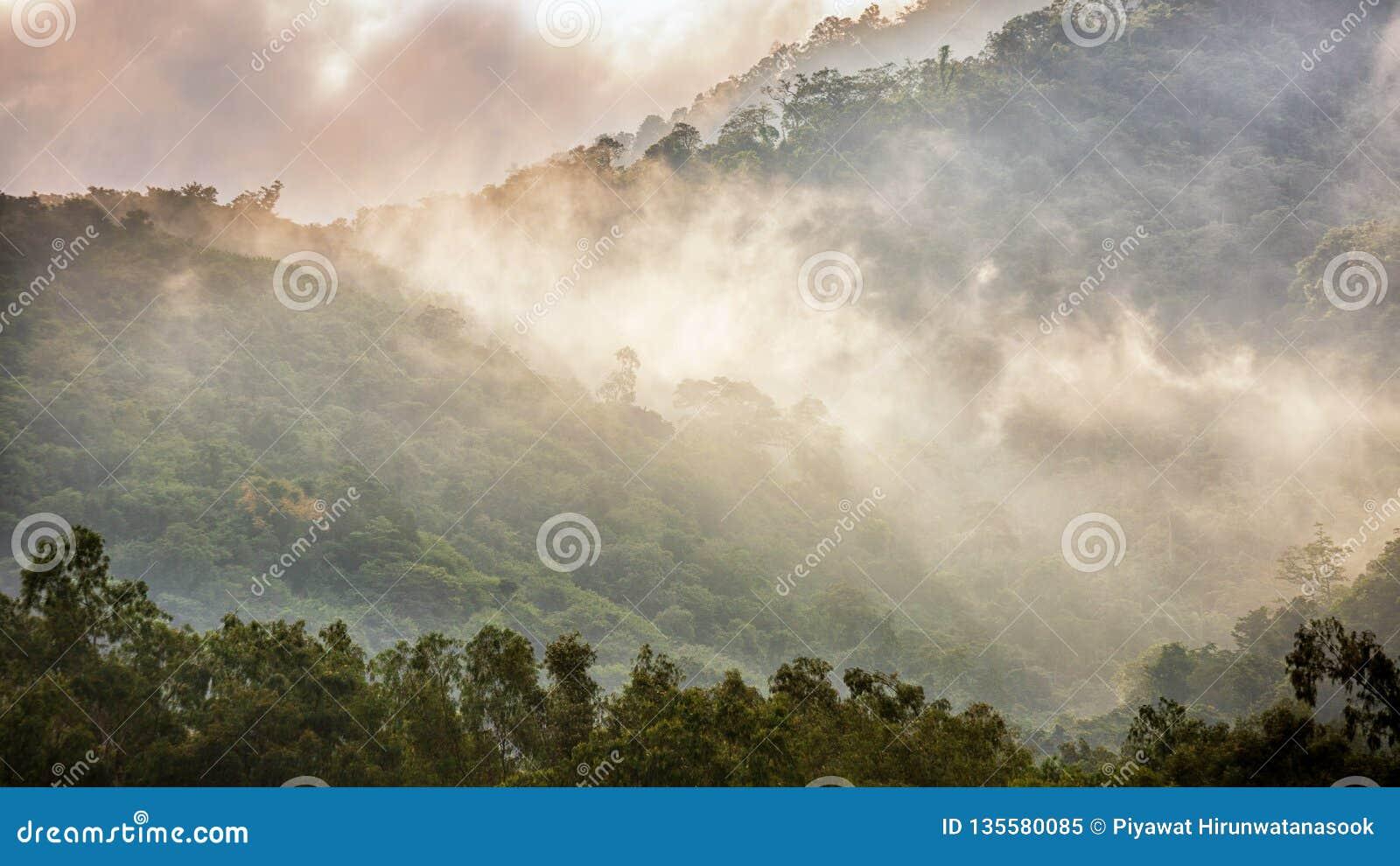éclat de lumière du soleil sur le brouillard sur la chaîne de montagne