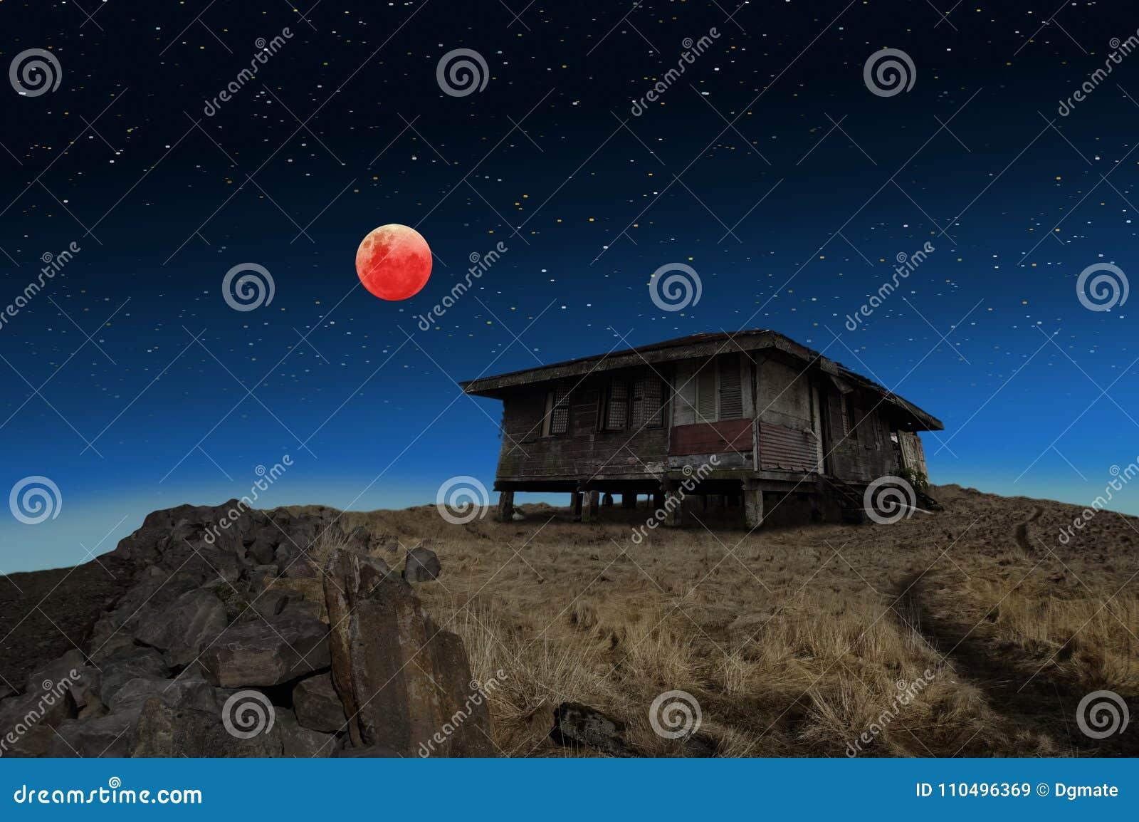 Éclipse superbe de lune de sang bleu et une vieille maison abandonnée