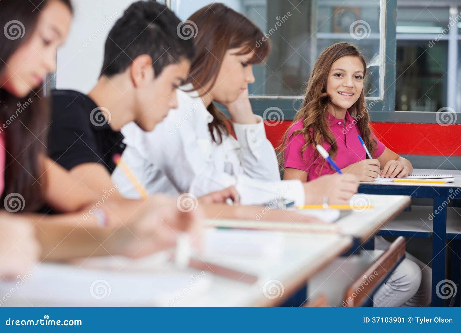Écolière adolescente s asseyant au bureau