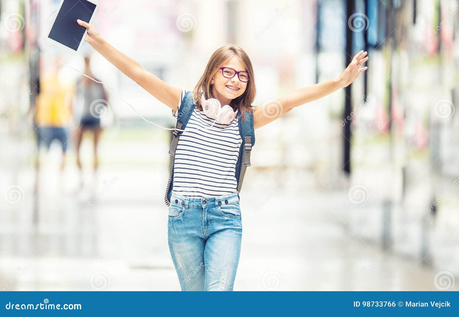 Écolière avec le sac, sac à dos Portrait de fille de l adolescence heureuse moderne d école avec les écouteurs et le comprimé de
