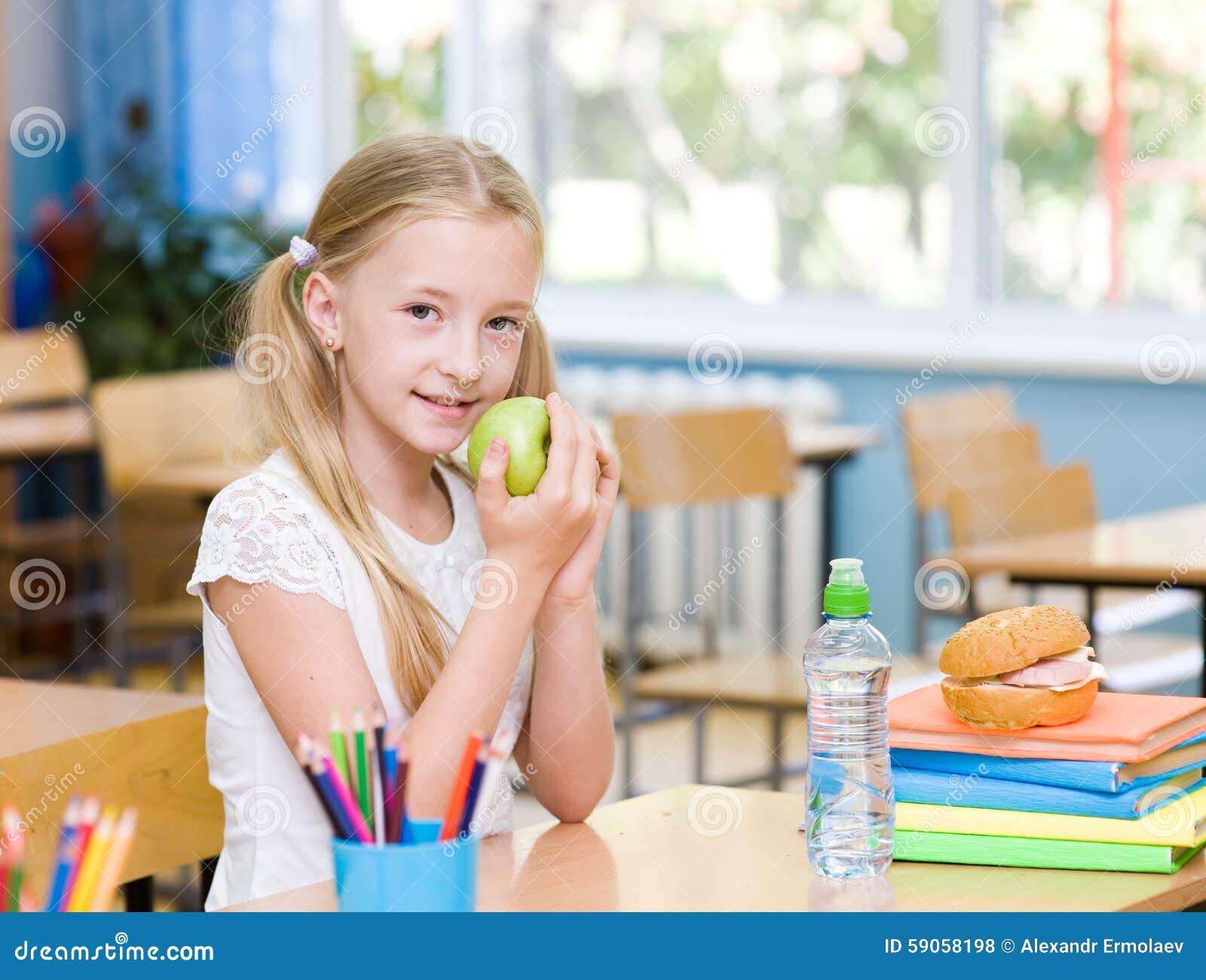 Écolière dans la salle de classe mangeant une pomme verte