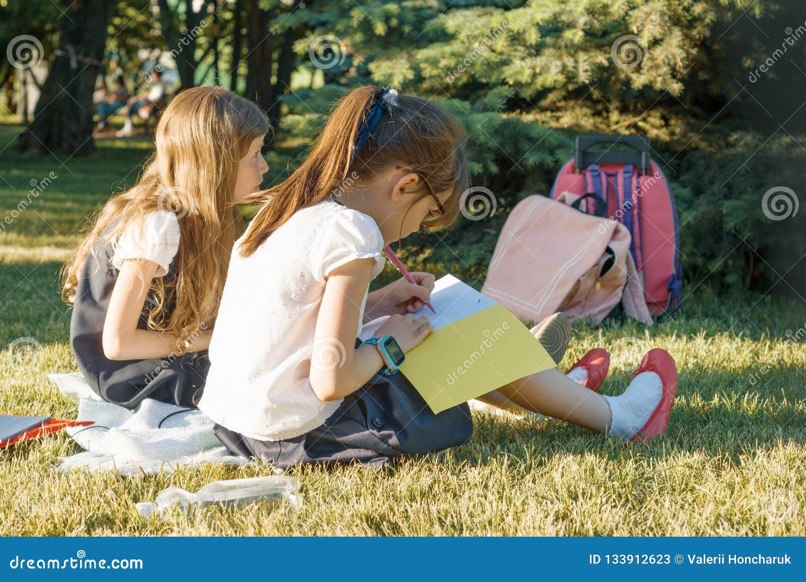 Écolière deux de petite amie apprenant la séance sur un pré en parc Enfants avec des sacs à dos, livres, carnets Vue de