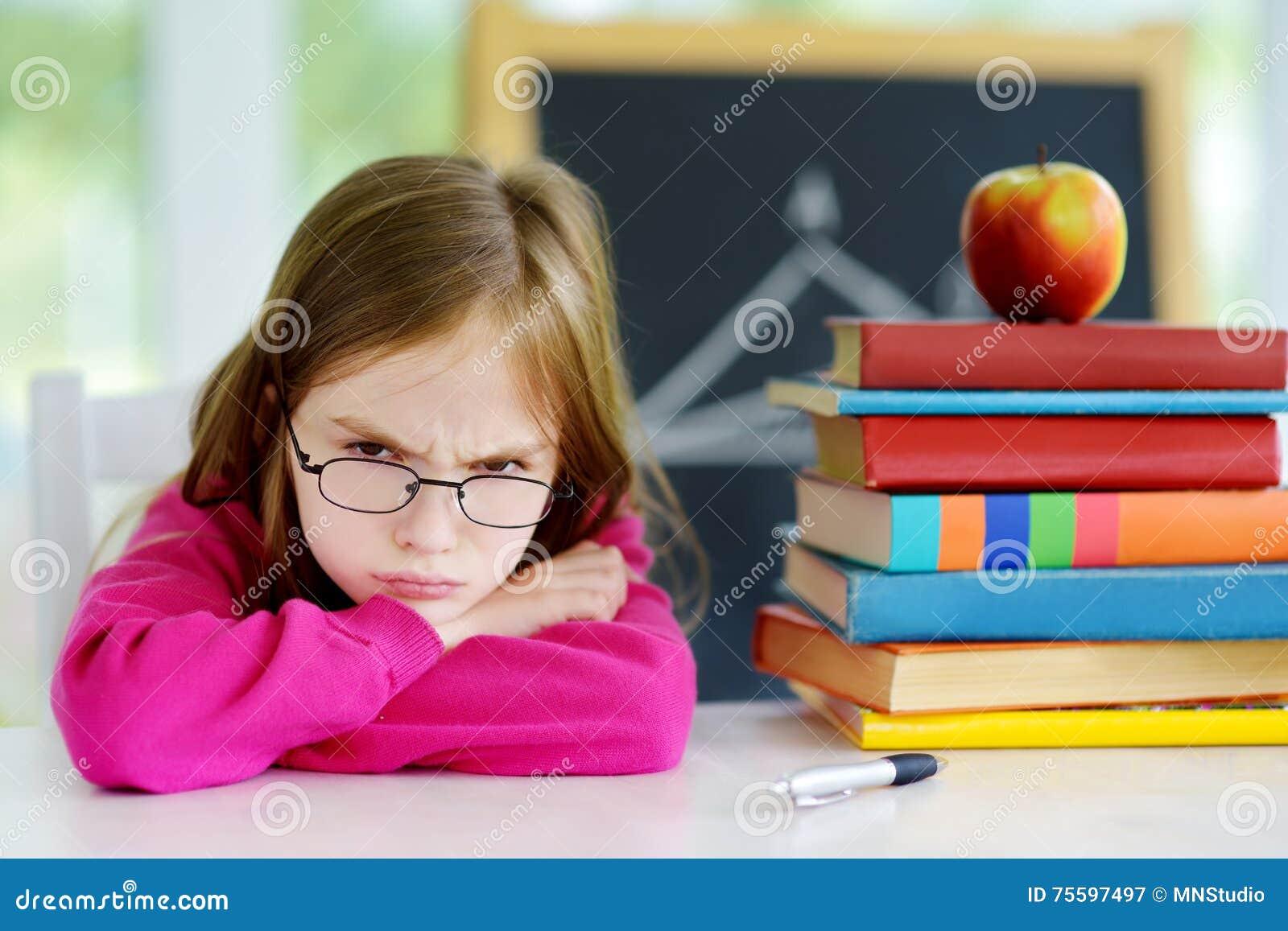Écolière fâchée et fatiguée étudiant avec une pile des livres sur son bureau