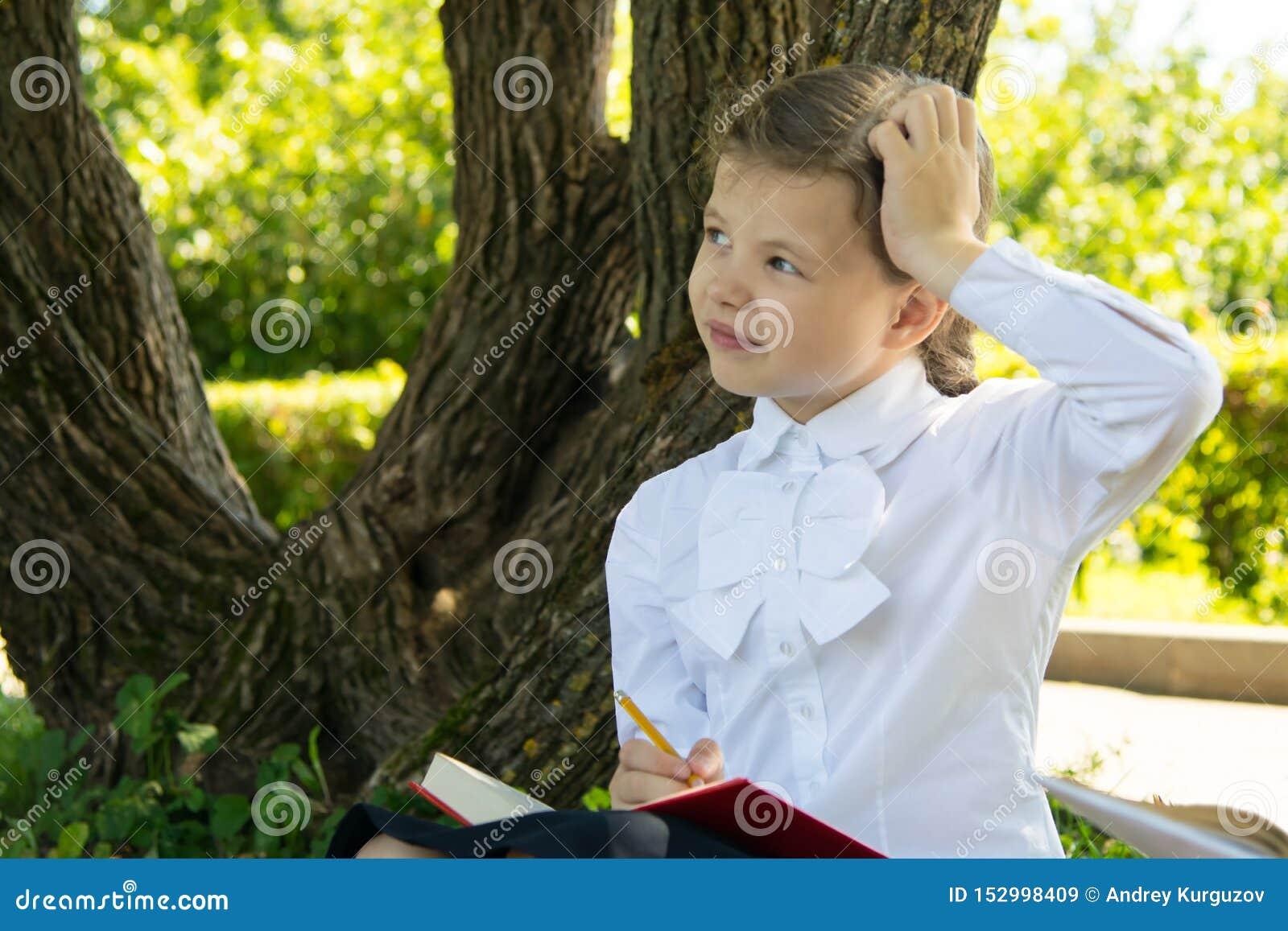 Écolière faisant le travail en parc à l air frais, pensant à la tâche et rayant sa tête, plan rapproché