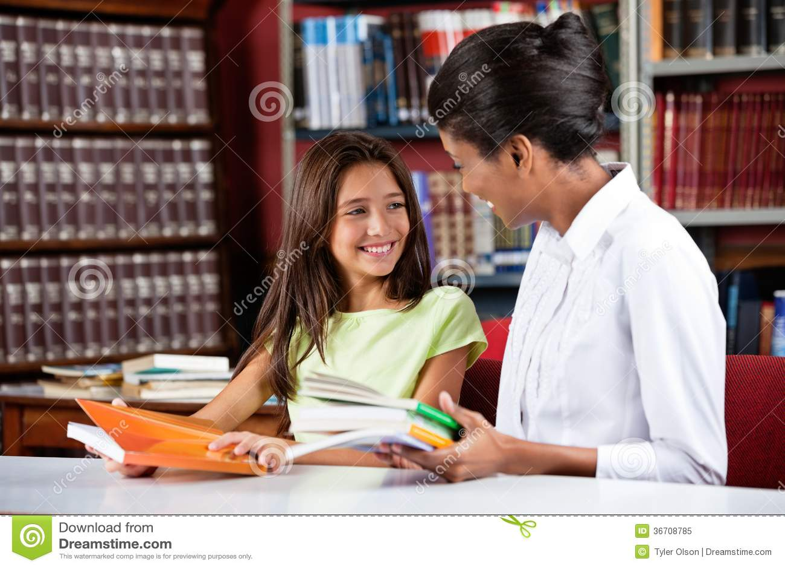 Écolière heureuse semblant le bibliothécaire féminin In