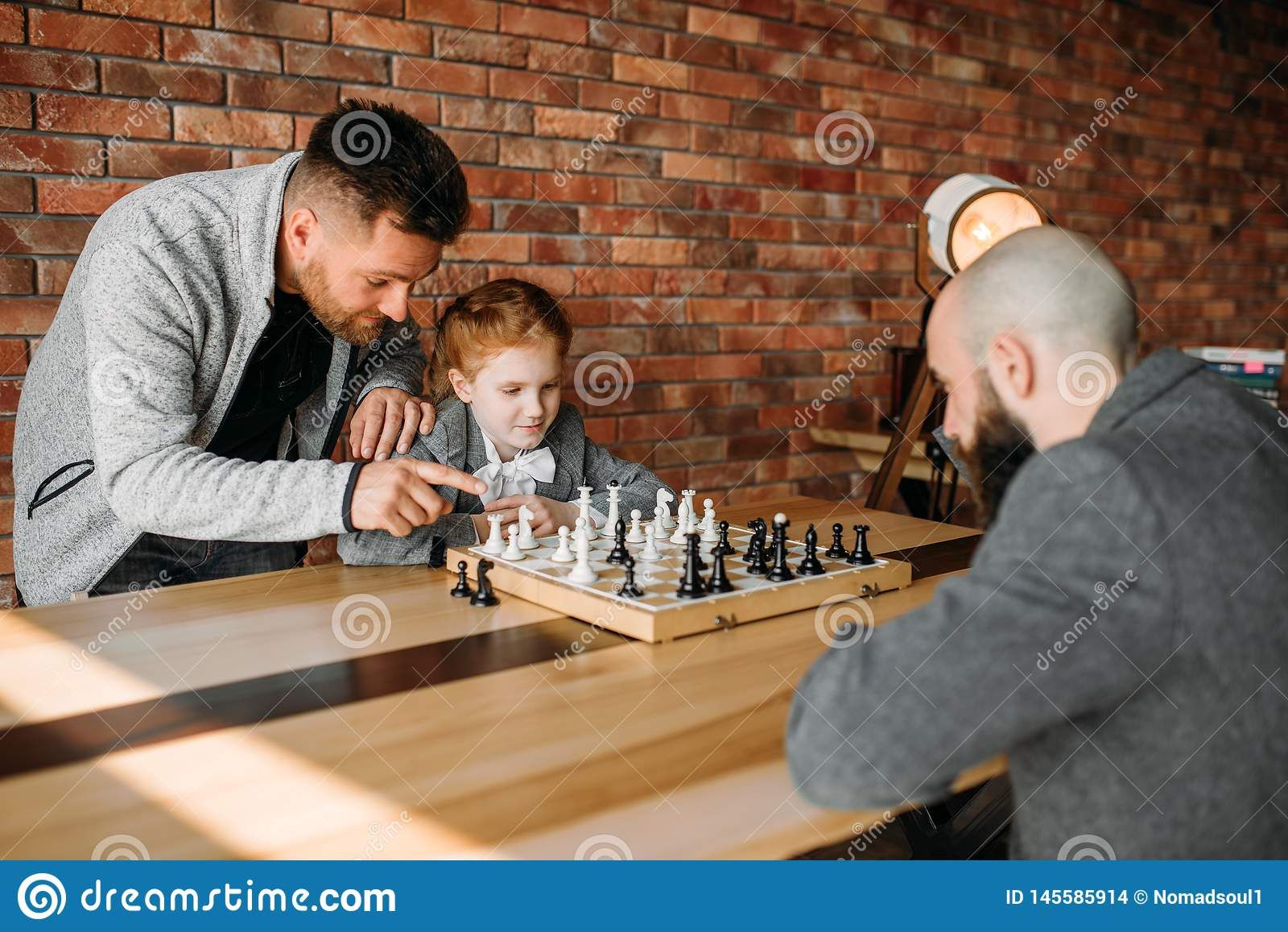 Écolière intelligente jouant aux échecs avec l homme
