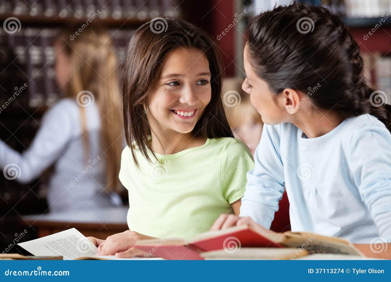Écolière regardant l ami féminin dans la bibliothèque