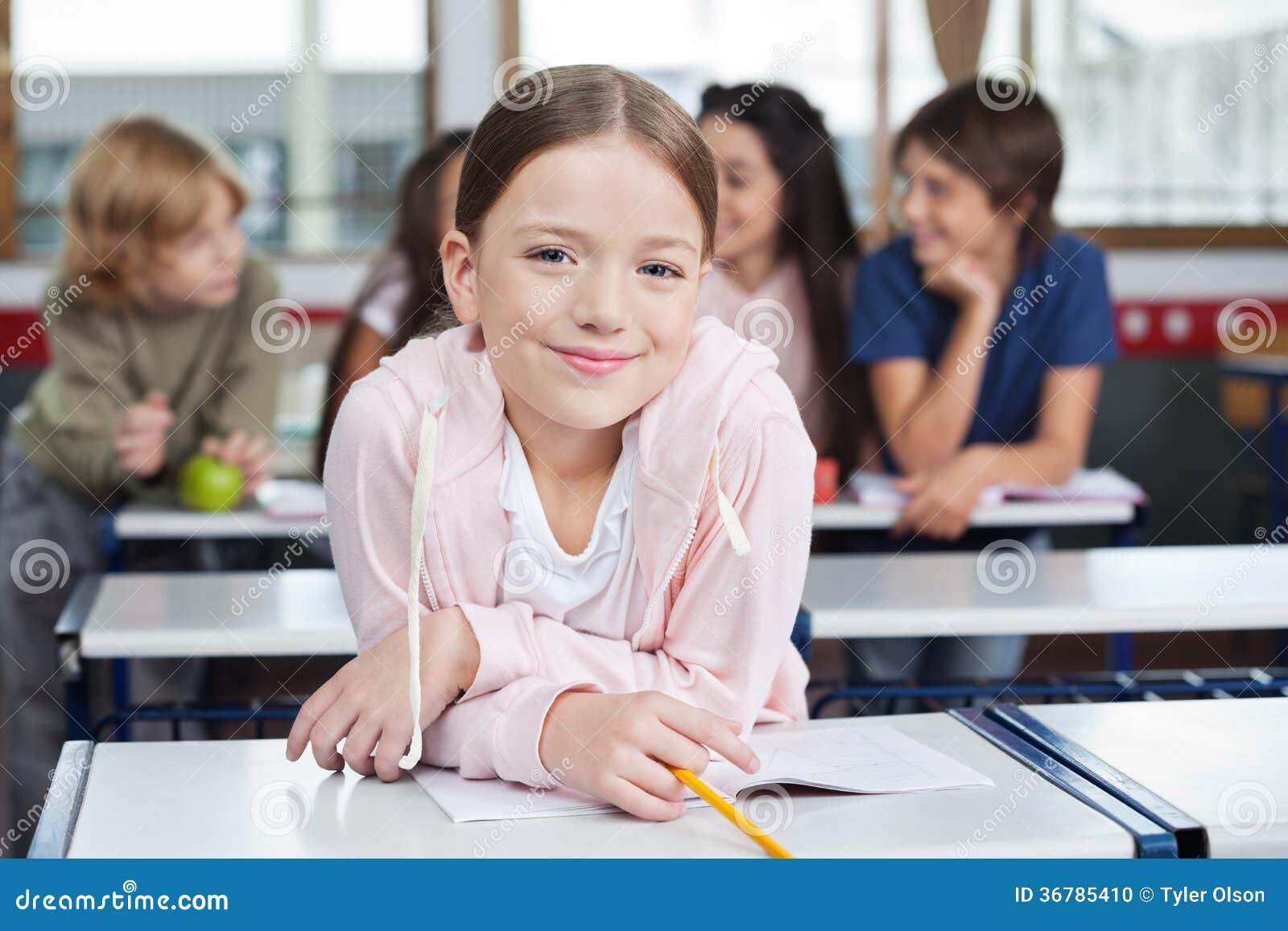 Écolière souriant tout en se penchant sur le bureau