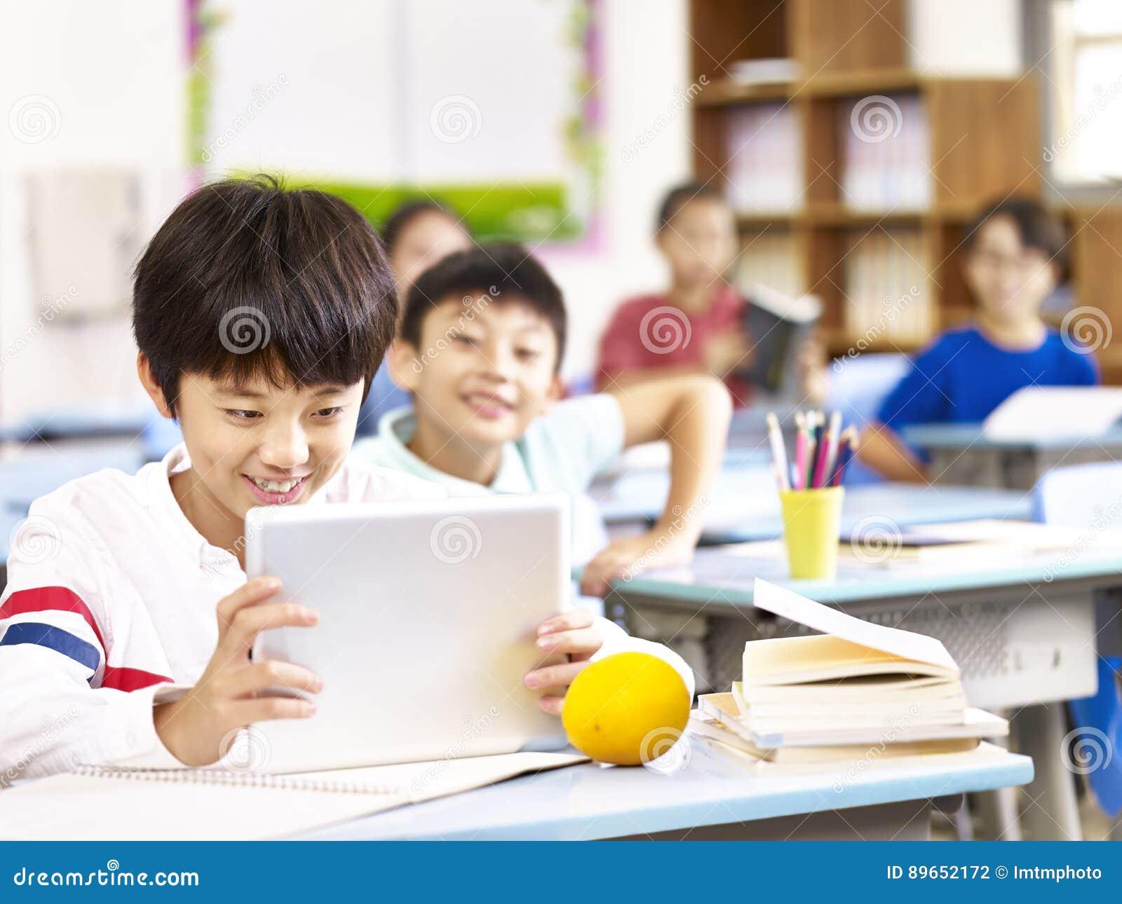 Écolier asiatique à l aide du comprimé dans la salle de classe