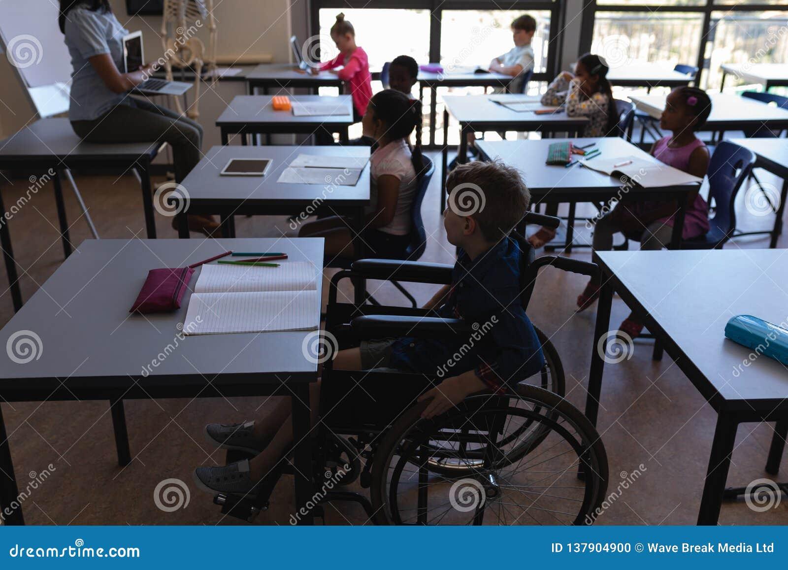 Écolier de débronchement avec des camarades de classe étudiant et s asseyant au bureau dans la salle de classe