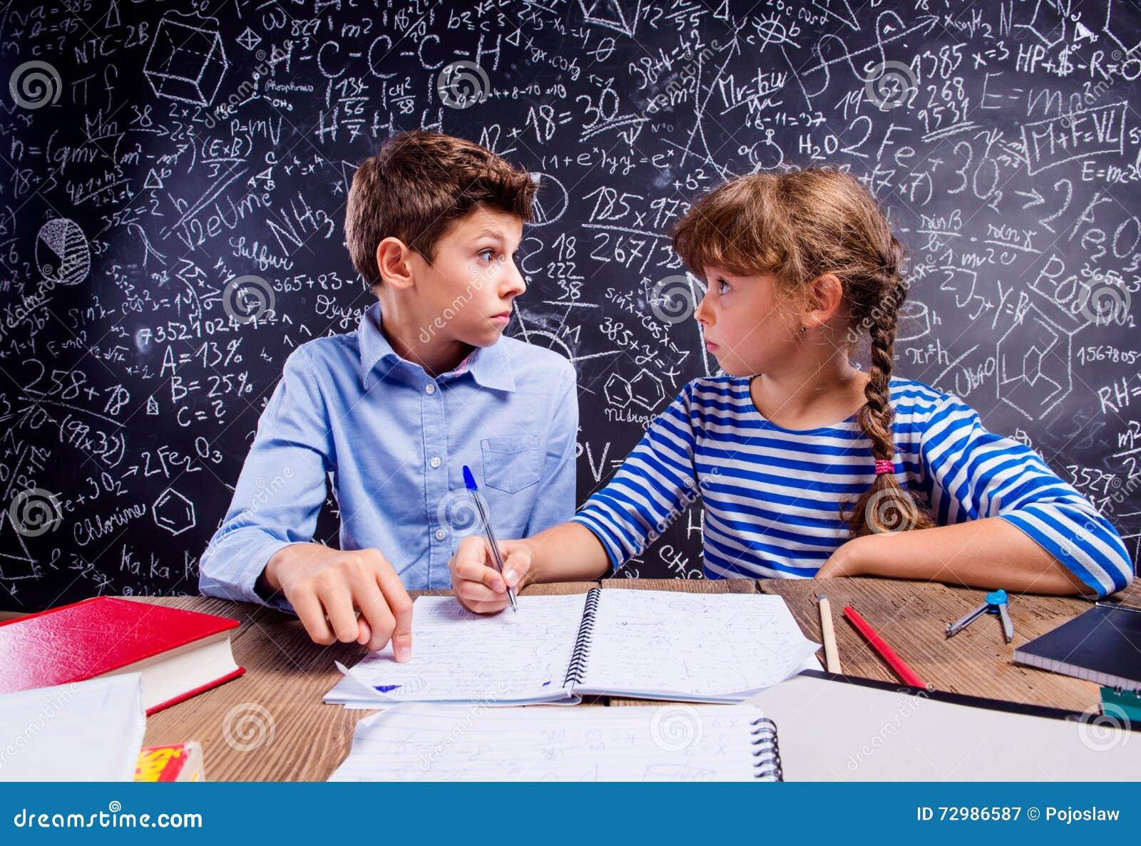 Écolier et fille au bureau grand tableau noir image stock image