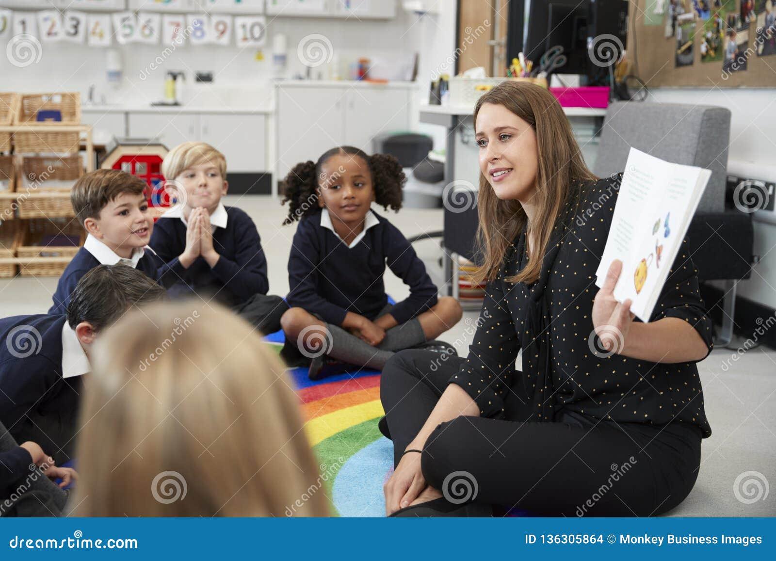 Écoliers primaires s asseyant sur le plancher dans la salle de classe avec leur professeur supportant un livre pour les montrer,