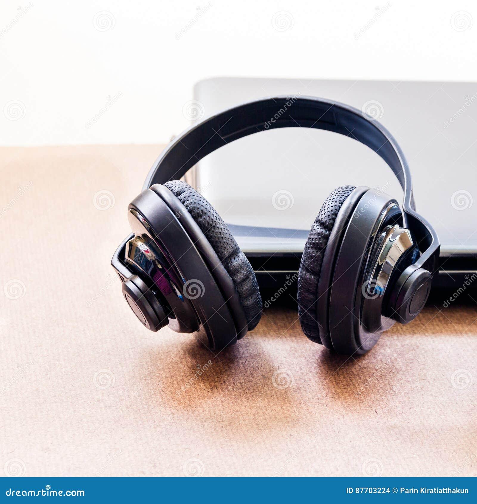 Écouteurs et ordinateur portable sur la table en bois