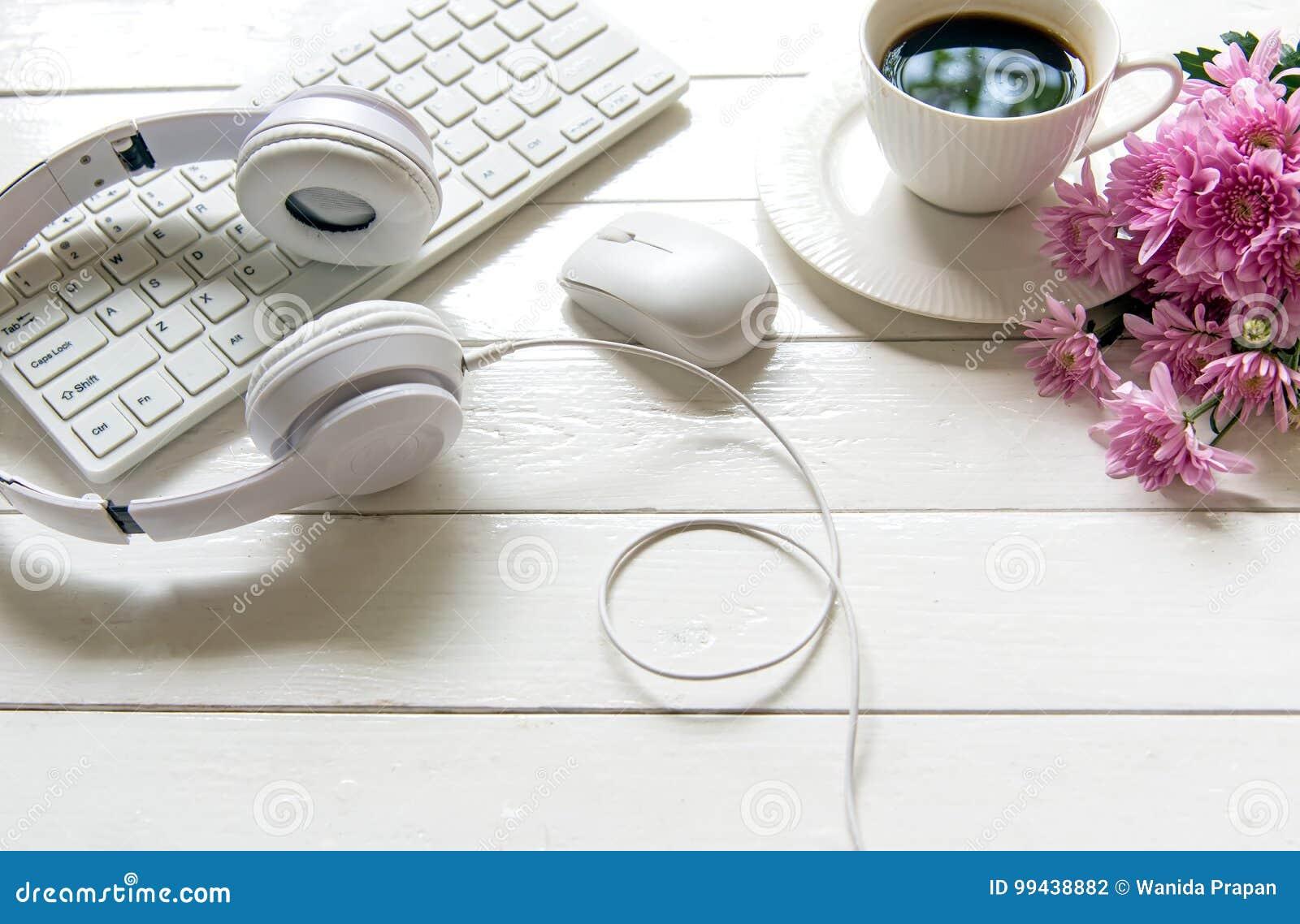 Écouteurs et tasse de café sur la table en bois de bureau avec la