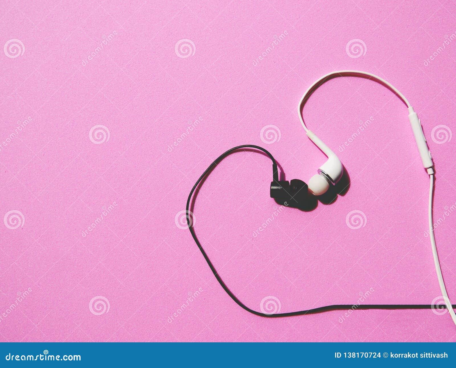 Écouteurs noirs et blancs avec des baisers en forme de coeur sur le fond rose