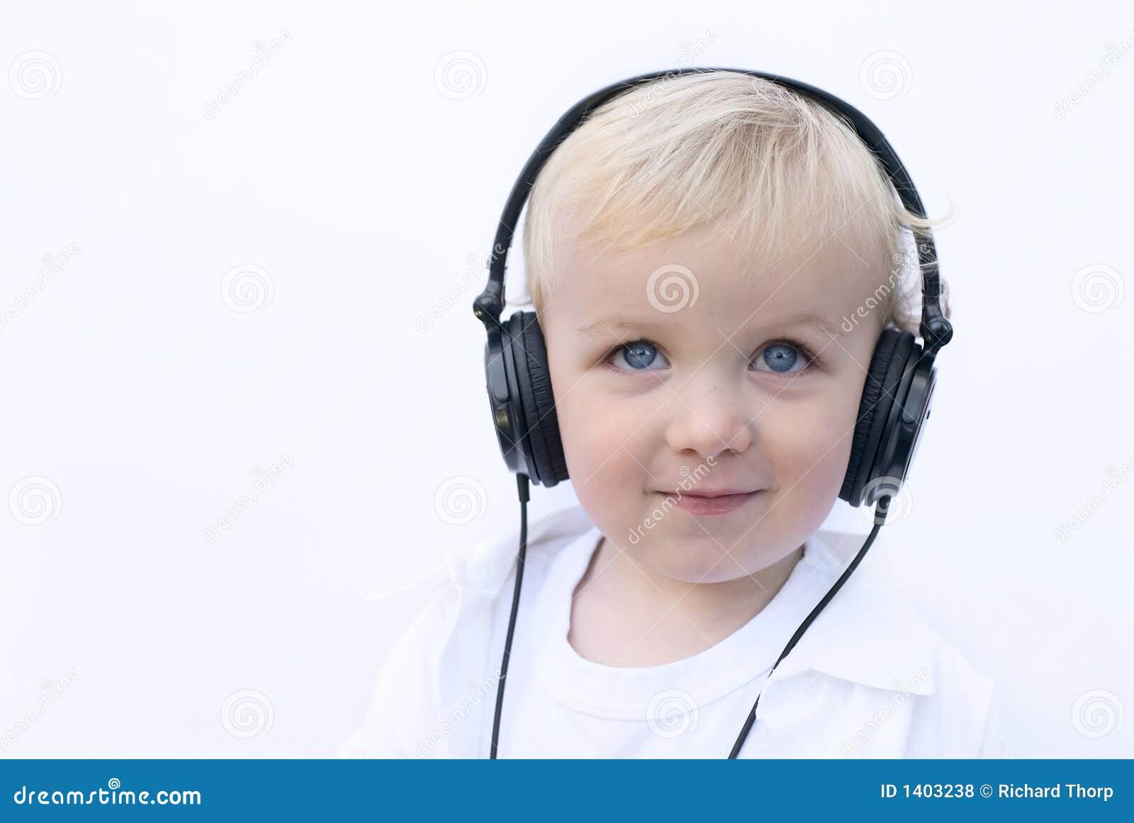 Écouteurs s usants de jeune garçon heureux